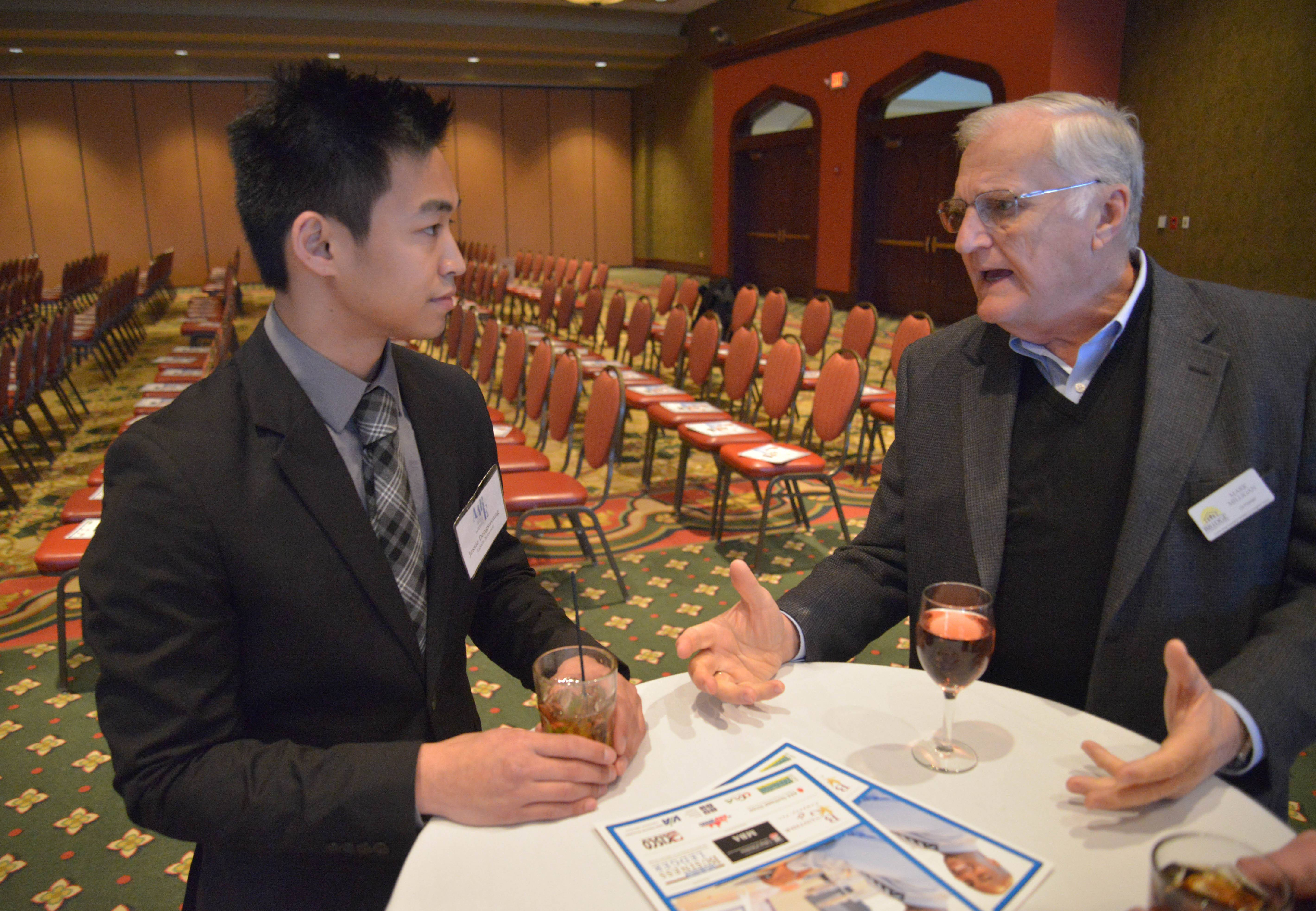 Paul Michna/pmichna@dailyherald.com Jessie Dengsavang of LaSalle Network talks to Mark Milligan of Bridge Communities during the  Daily Herald Business Ledger AABE awards Wednesday March 12, at Medinah Banquets in Addison.