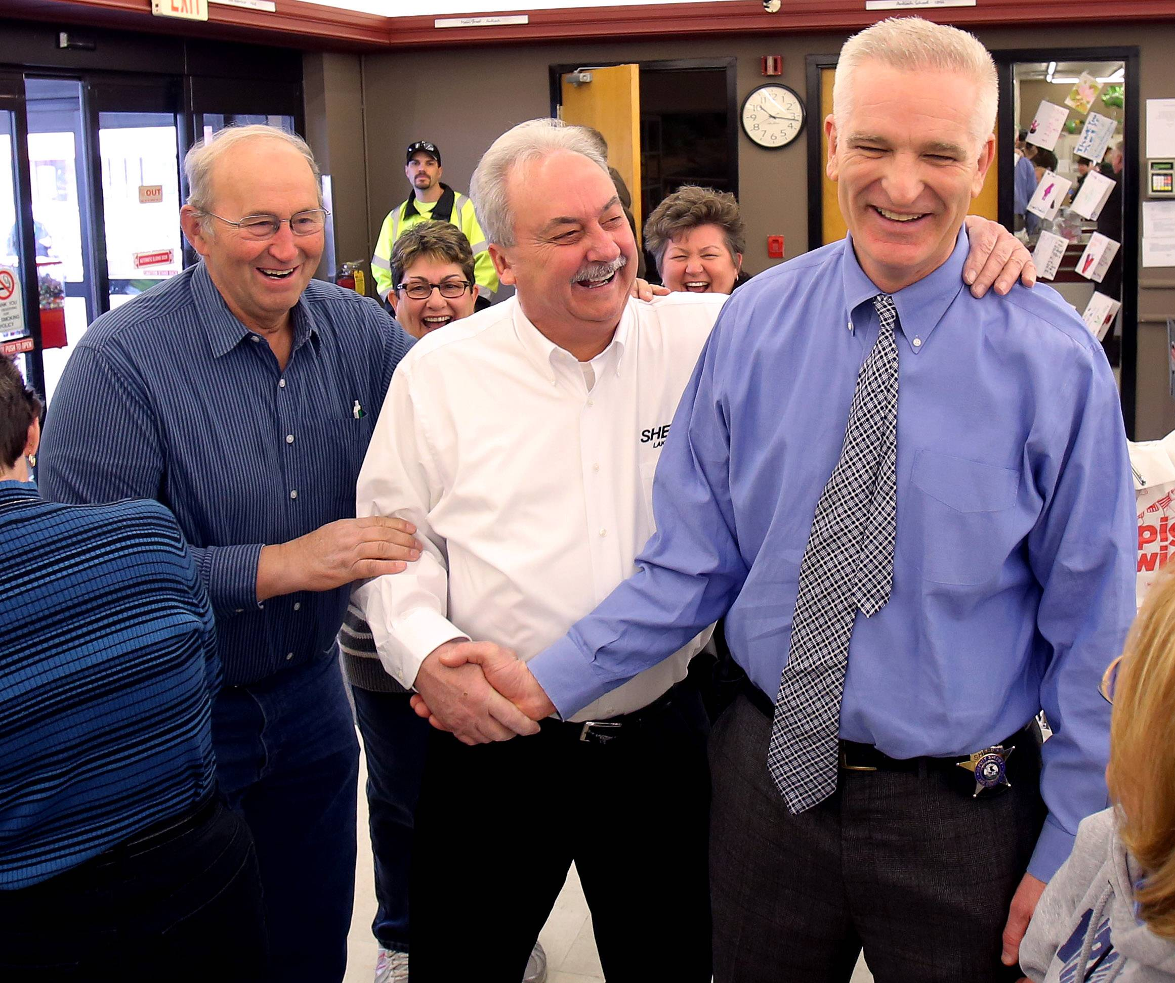 Former Fremont Township Supervisor Pete Tekampe, left, and Lake County Undersheriff Ray Rose, middle, congratulate Lake County Sheriff Mark Curran for his victory Thursday in the Lake County Farm Bureau's 16th Annual Race for Hunger at Piggly Wiggly in Antioch.