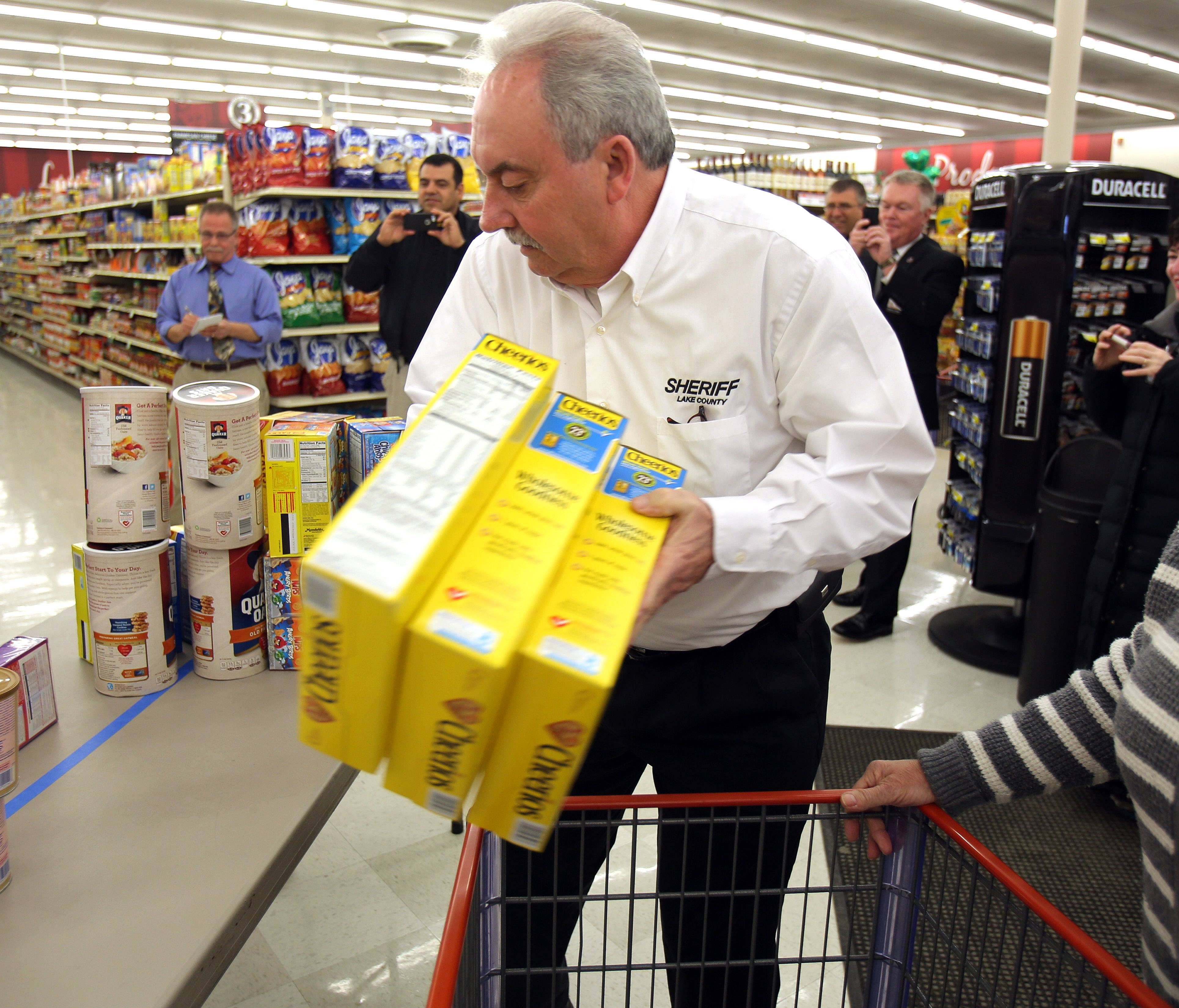 Lake County Undersheriff Ray Rose loads a cart Thursday at the Piggly Wiggly store in Antioch during the 16th Annual Race for Hunger. Rose and Sheriff Mark Curran had five minutes to fill their carts with nonperishable items for local food pantries.