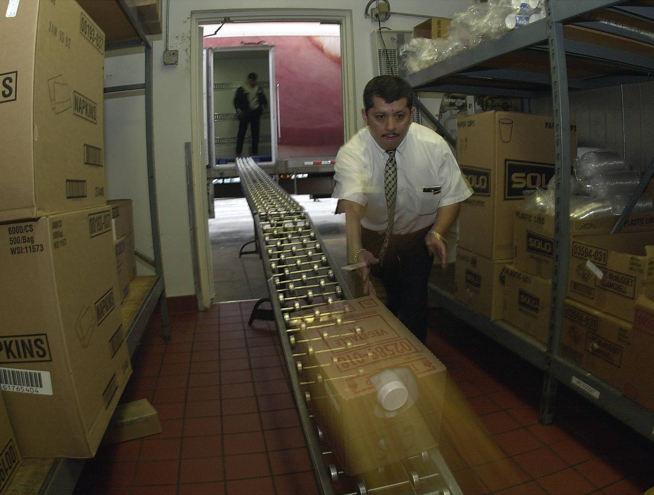 Assistant Manager of the toll plaza McDonald's Feliciano Herrera unloads the supply truck in the backroom.