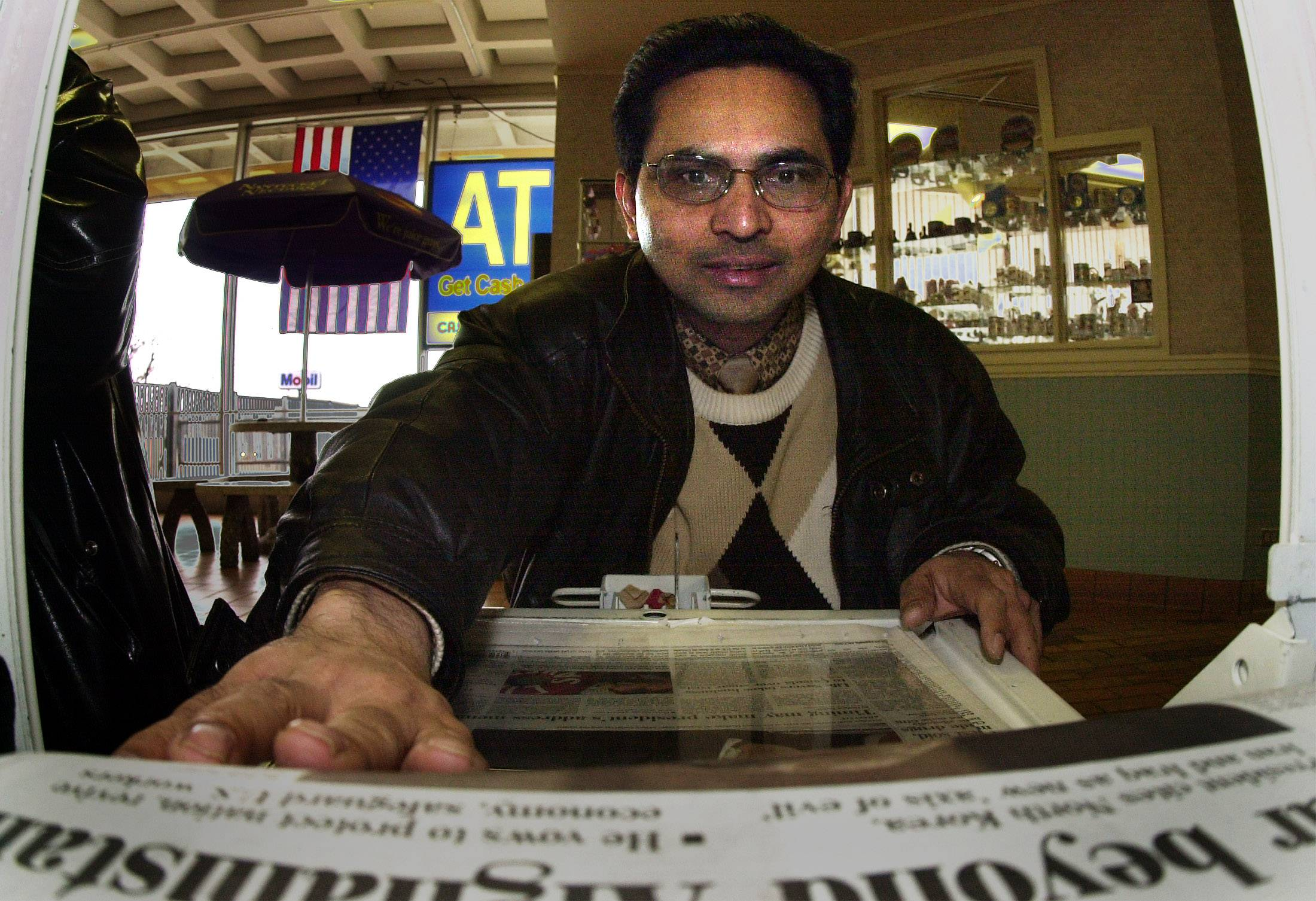 Arif Mohammed of Palatine grabs a newspaper from the newspaper box for his 12:30 lunch at the Des Plaines oasis.