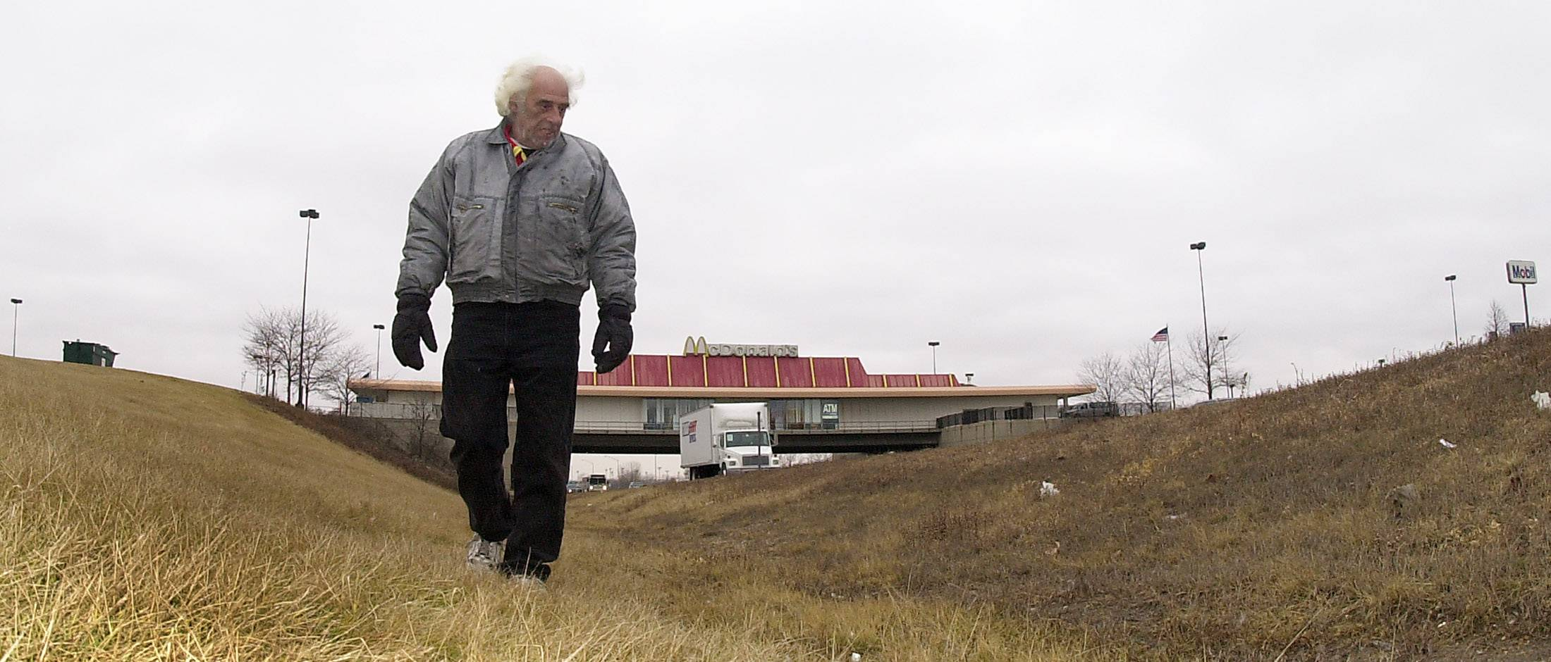 Looking for cigarette packages with UPC codes, Richard David of Wooddale walks along the tollway next to the highway looking to collect. He uses the codes to send in and get clothes and other items offered through the company.
