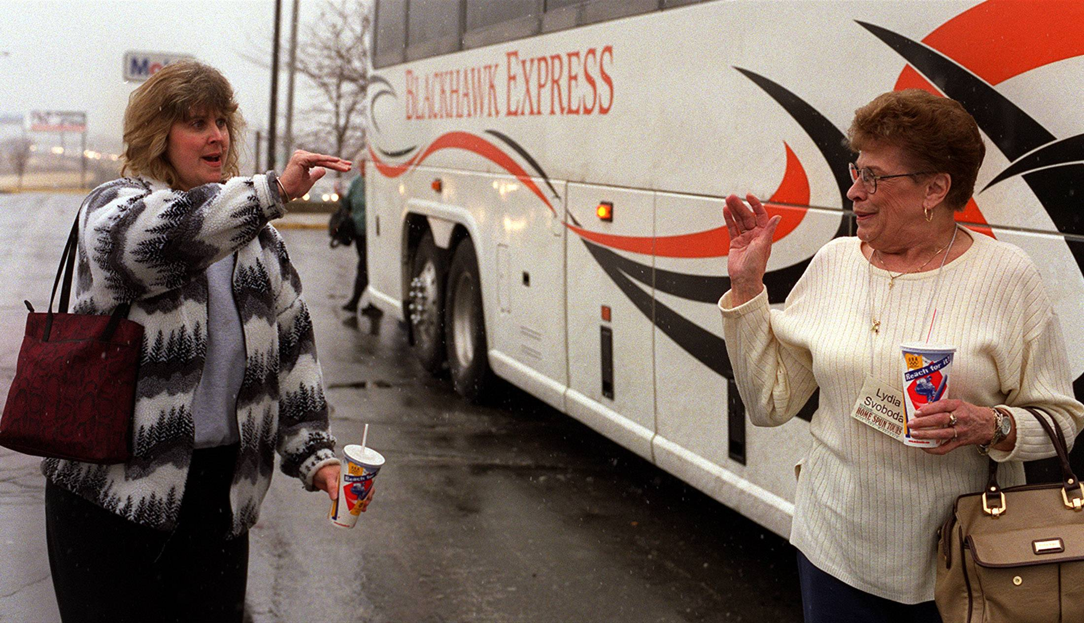 Ann Vujica, left, of Berwyn waves to her mother Lydia Svoboda of Rice Lake, Wi. Ann's mother was on a tour bus which briefly stopped at the oasis before journeying toward the East Coast.