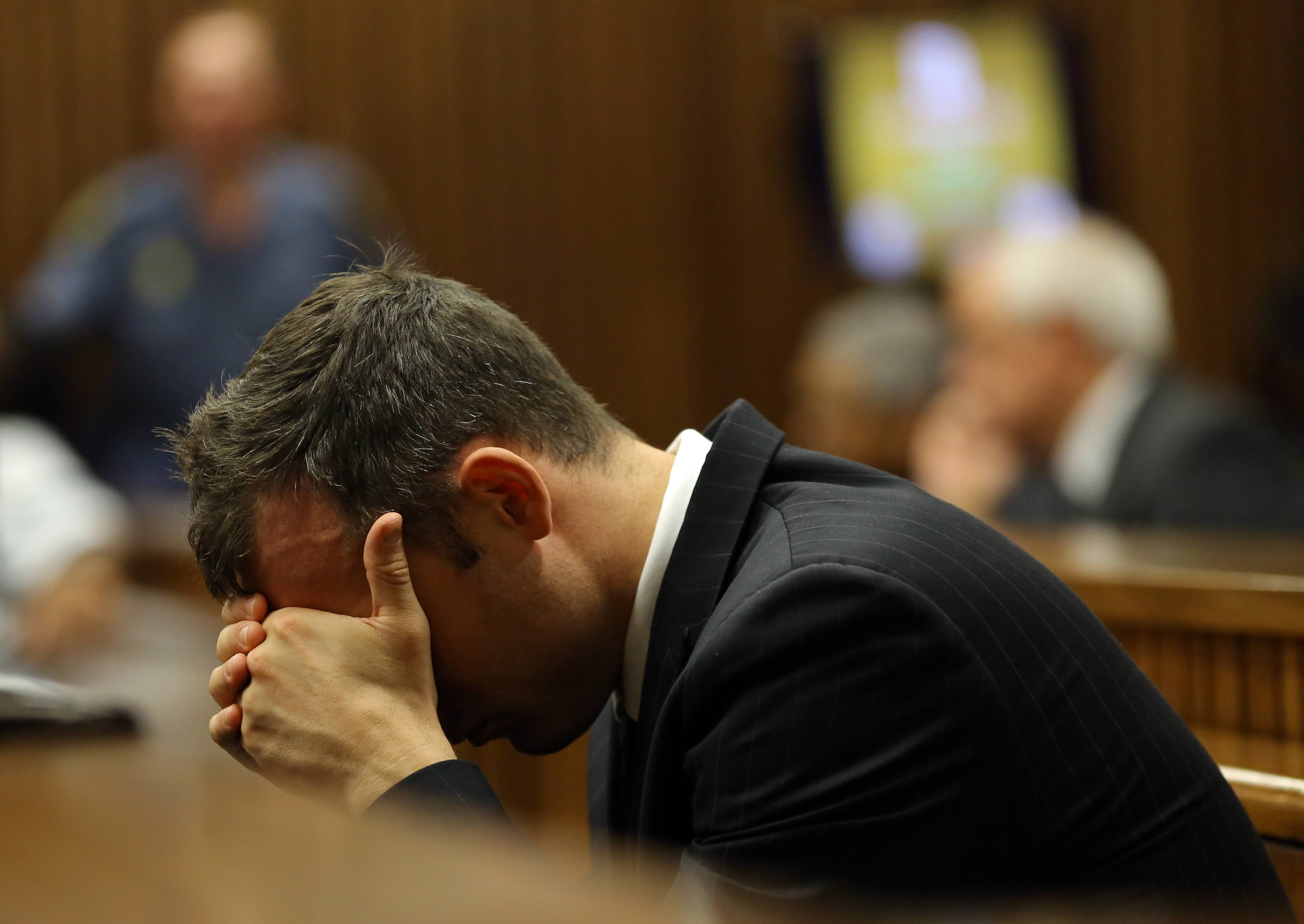 Oscar Pistorius places his head in his hands as he listens to the cross examination during his trial in court in Pretoria, South Africa, Thursday. He is charged with the shooting death of his girlfriend Reeva Steenkamp on Valentine's Day in 2013.