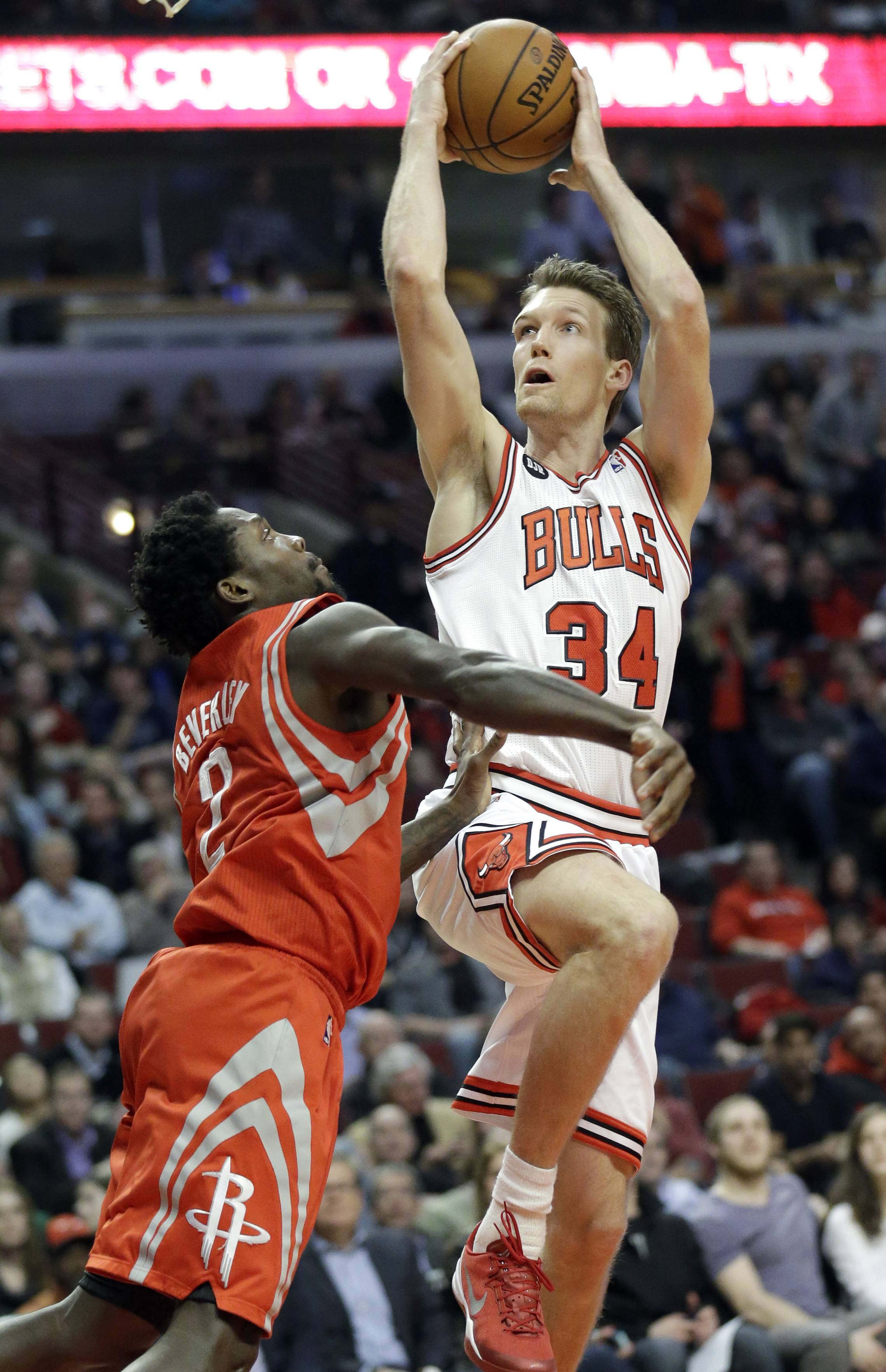 Wearing a bandage over his right eye after taking 10 stitches, Bulls guard Mike Dunleavy drives to the basket against Houston's Patrick Beverley in the second half Thursday night.
