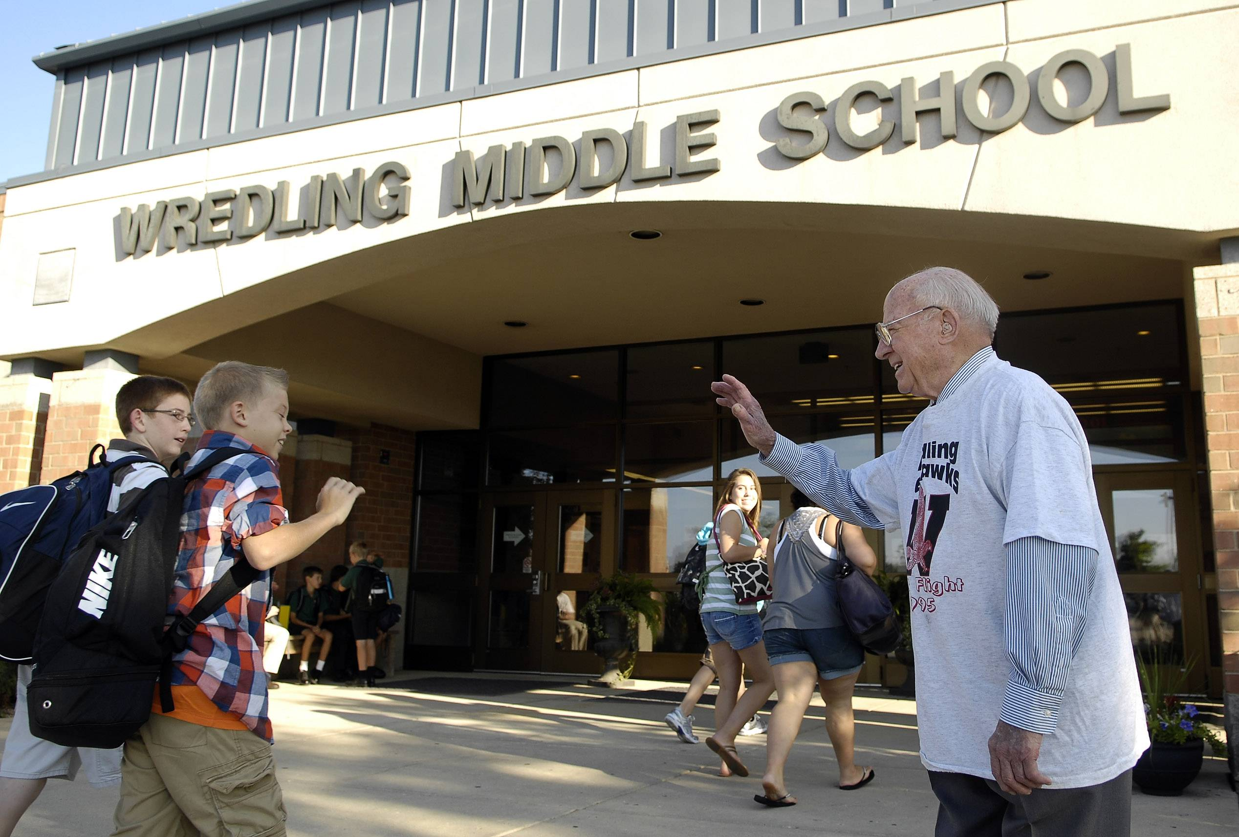 John Wredling, here greeting students before the first day of school at Wredling Middle School, will be the grand marshal of the St. Charles St. Patrick's Day Parade. Wredling, a former St. Charles District 303 superintendent, will be celebrating his 100th birthday Monday.