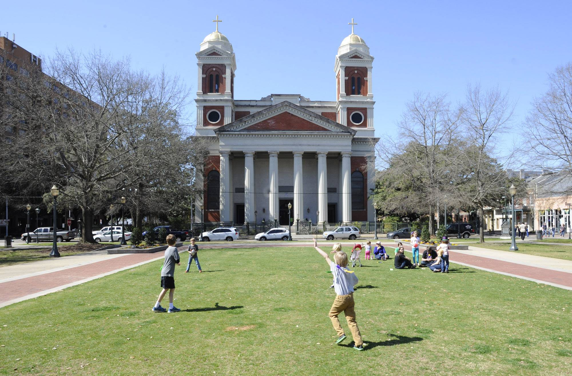 Children play in a park near the Cathedral Basilica of the Immaculate Conception in Mobile, Ala. The church is among the free attractions in Mobile.