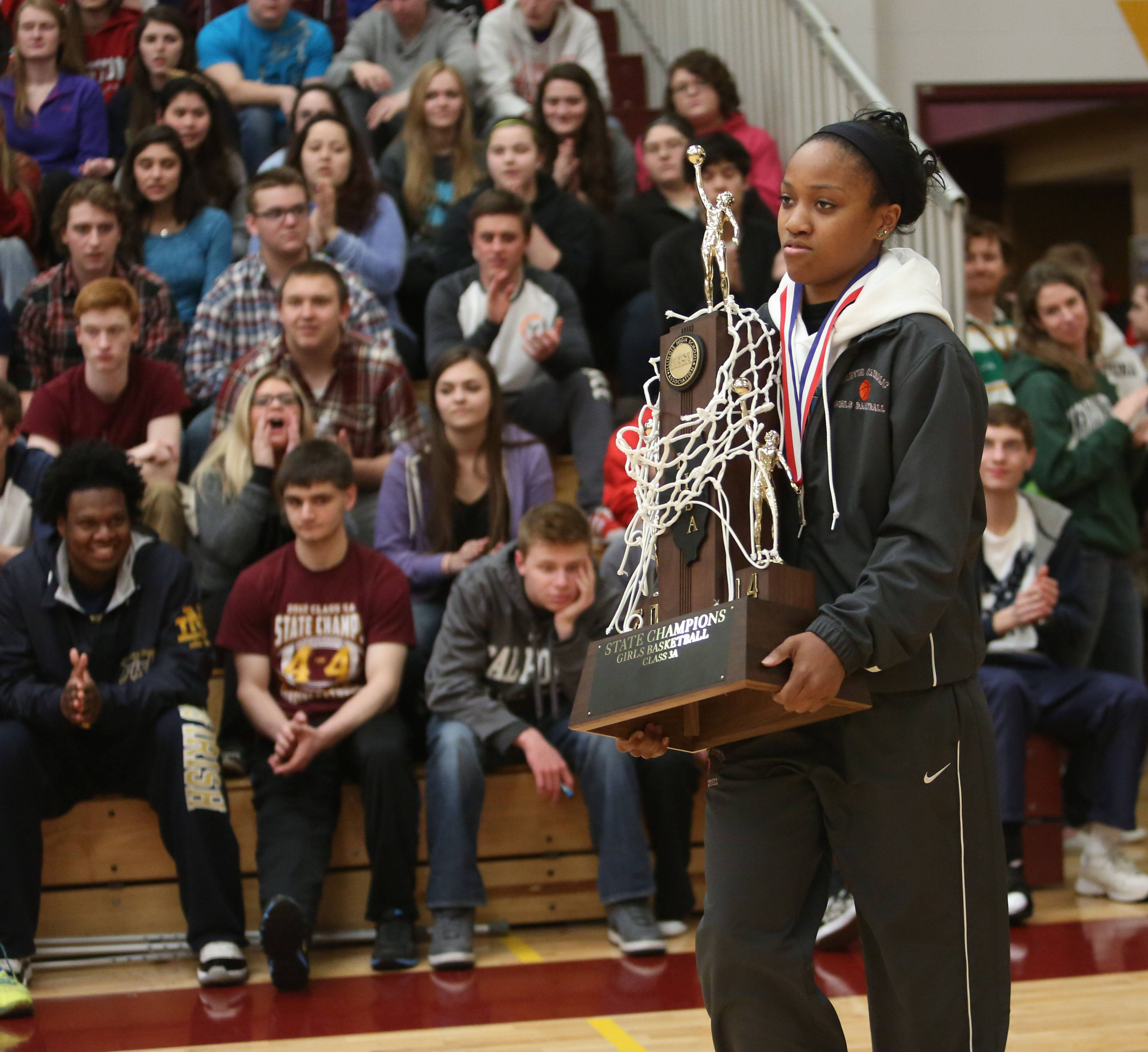 Sara Ross carries out the state championship trophy for the Montini Catholic High School girls basketball team during a pep rally Friday at the school. The team is celebrating its fourth state title in five years.