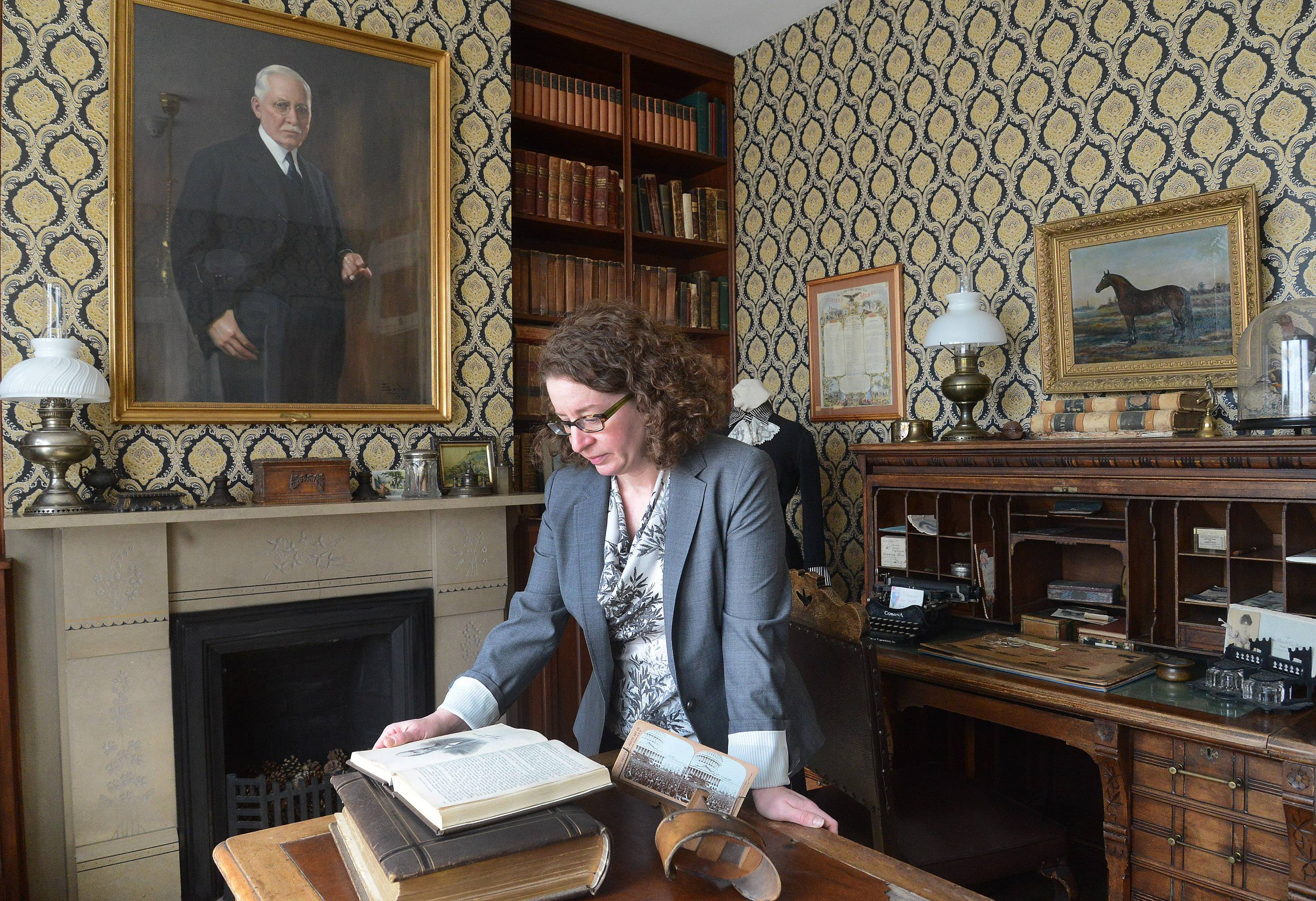 Jenny Barry, local history librarian at the Cook Memorial Library, looks over some historical books inside the Ansel B. Cook House in Cook Park.
