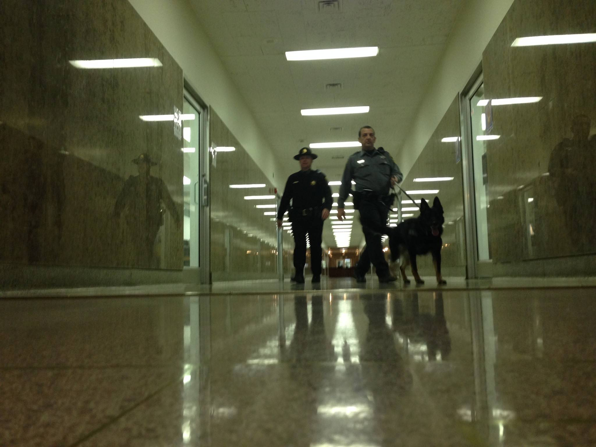 Two Secretary of State police officers walk in the hallway by state Rep. Keith Farnham's Springfield office Friday afternoon.
