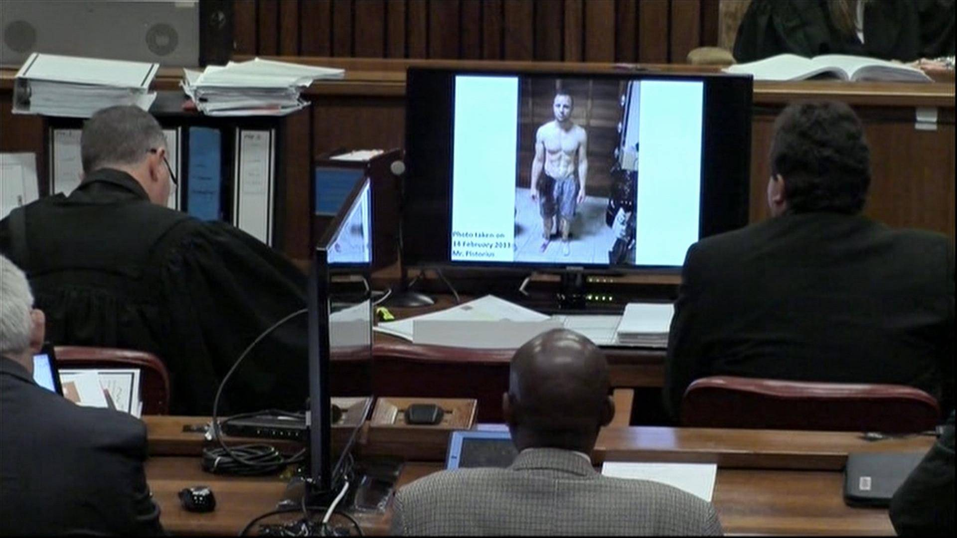 A police photograph of Oscar Pistorius standing on his bloodstained prosthetic legs and wearing shorts covered in blood, taken shortly after the athlete fatally shot his girlfriend, which was shown to the court in Pretoria, at his murder trial Friday, March 14, 2014.
