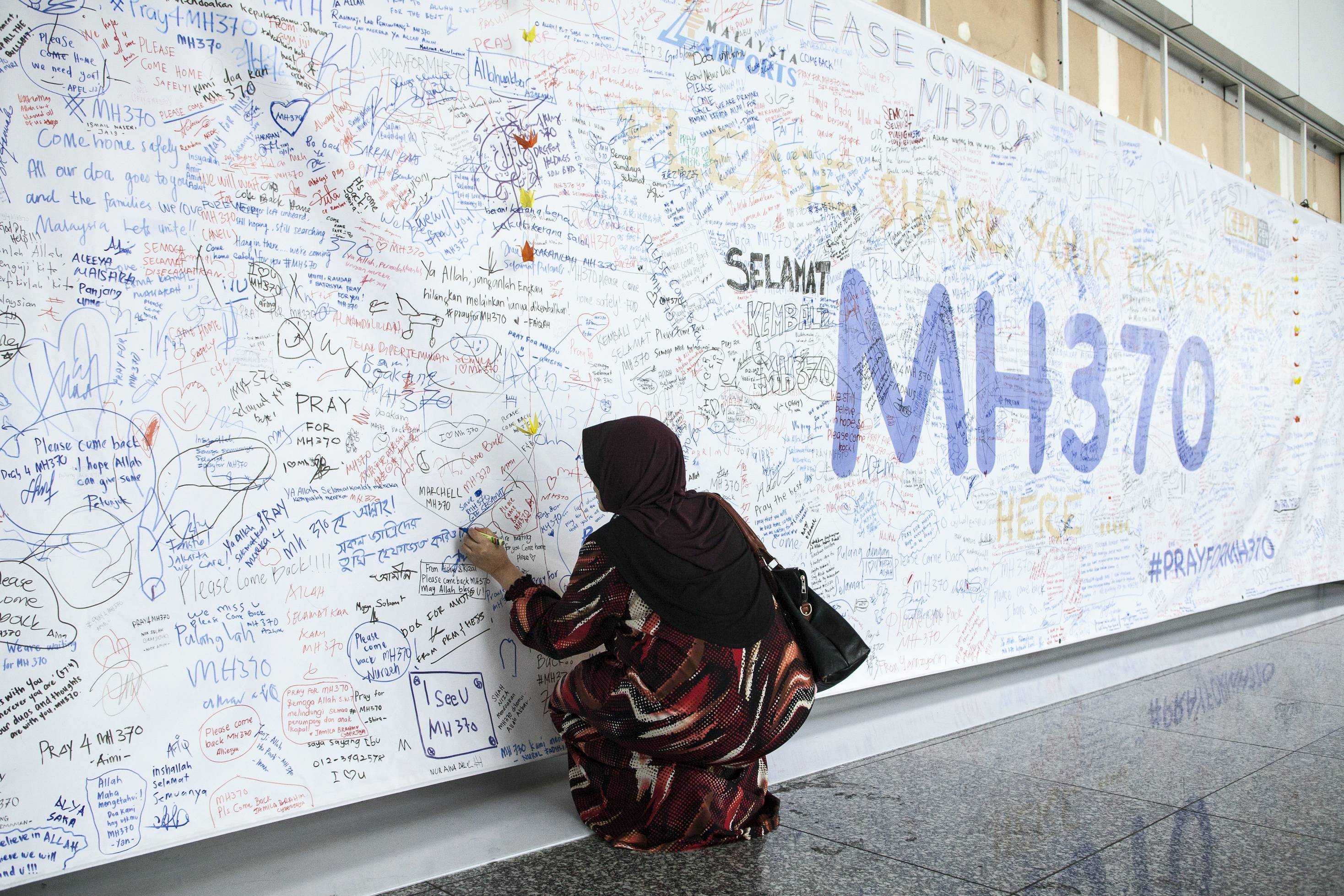 A woman writes a message on a banner for missing Malaysian Airline System Bhd. (MAS) Flight 370 at Kuala Lumpur International Airport (KLIA) in Sepang, Malaysia, on Friday, March 14, 2014.