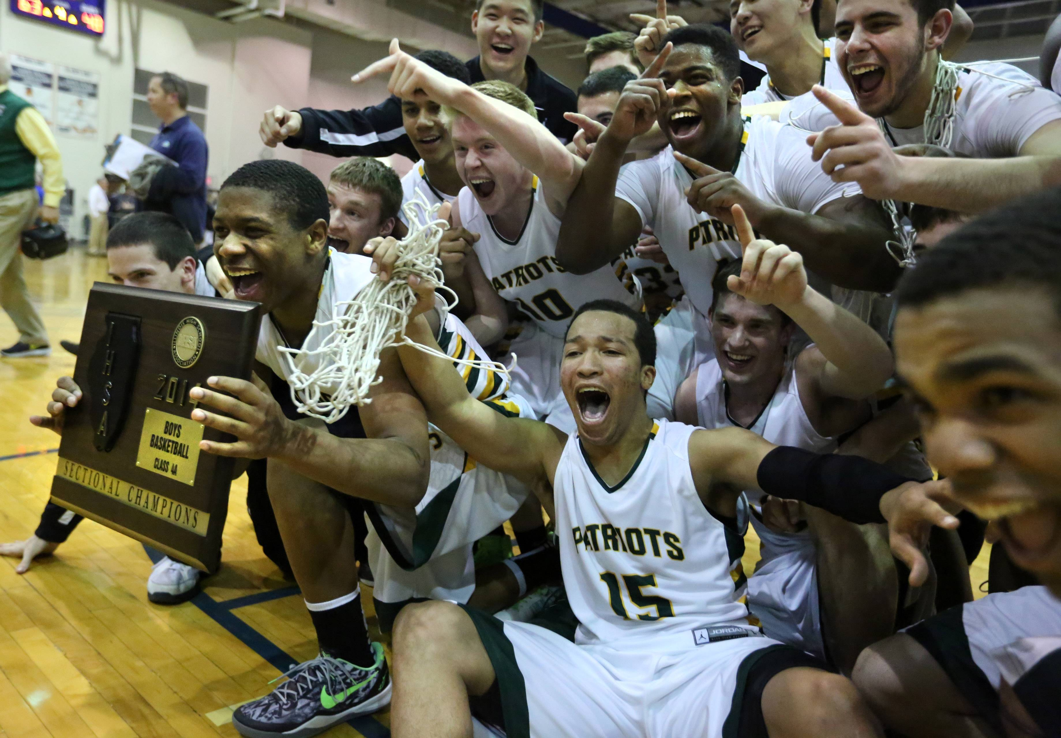 Stevenson's Matt Johnson, holding plaque, and Jalen Brunson, center, celebrate.