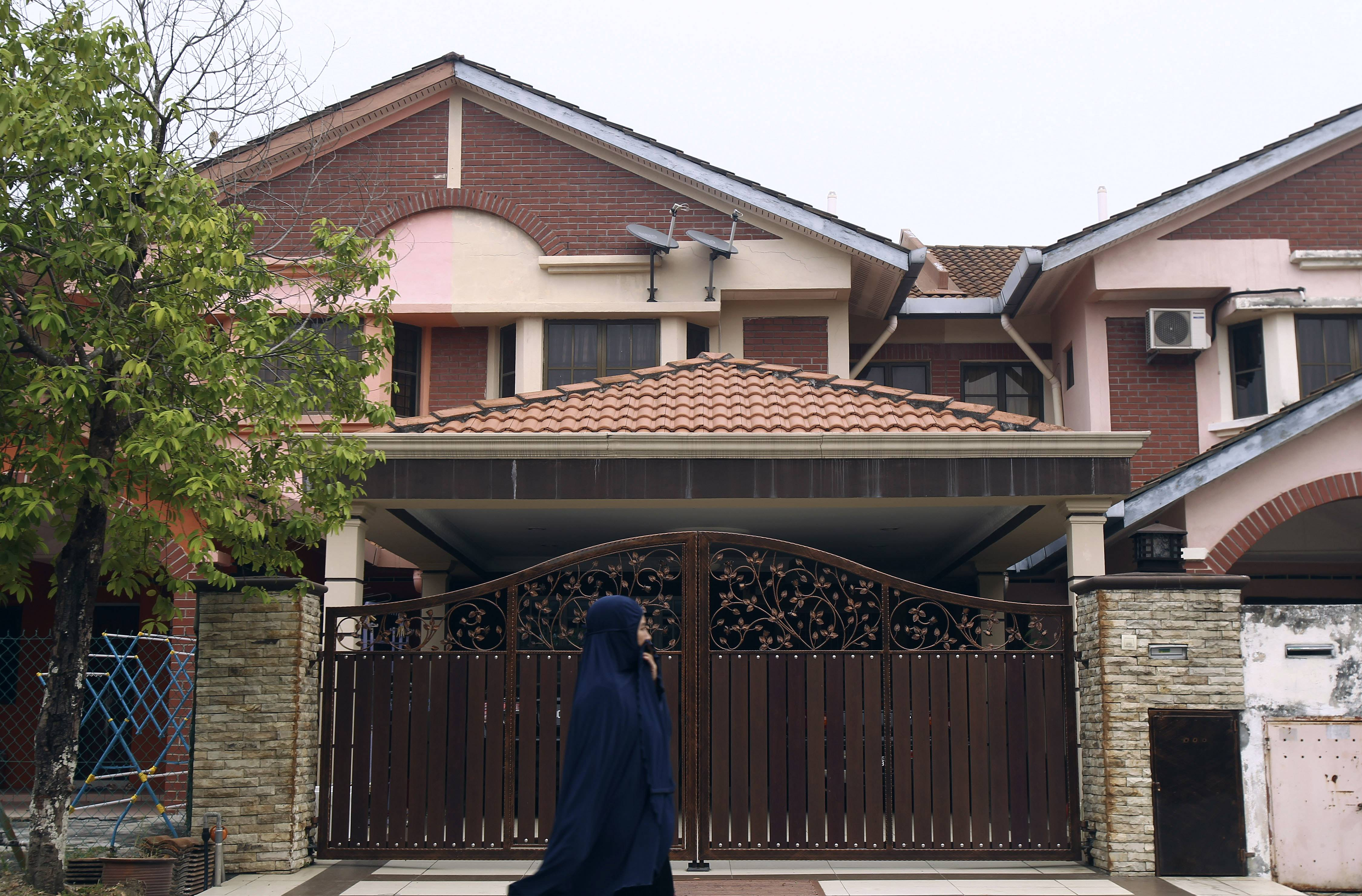 A woman walks past the missing Malaysia Airlines co-pilot Fariq Abdul Hamid's house in Shah Alam, outside Kuala Lumpur, Malaysia, Friday, March 14, 2014.