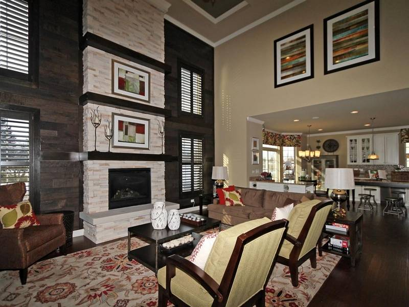 a dramatic floor to ceiling stone fireplace draws your attention in the family - Model Home Interior Design