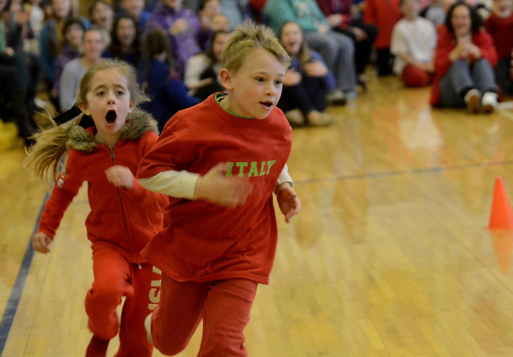 First-graders Briana Butler and Gavin Stanley race around the speed skating track during an Olympic event Friday at St. Francis de Sales Catholic School in Lake Zurich.