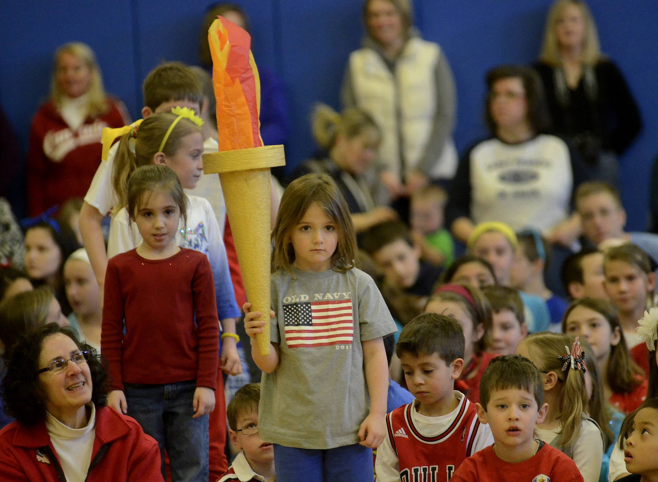 Kindergartner Layne Nordstrom carries the torch Friday at St. Francis de Sales Catholic School.