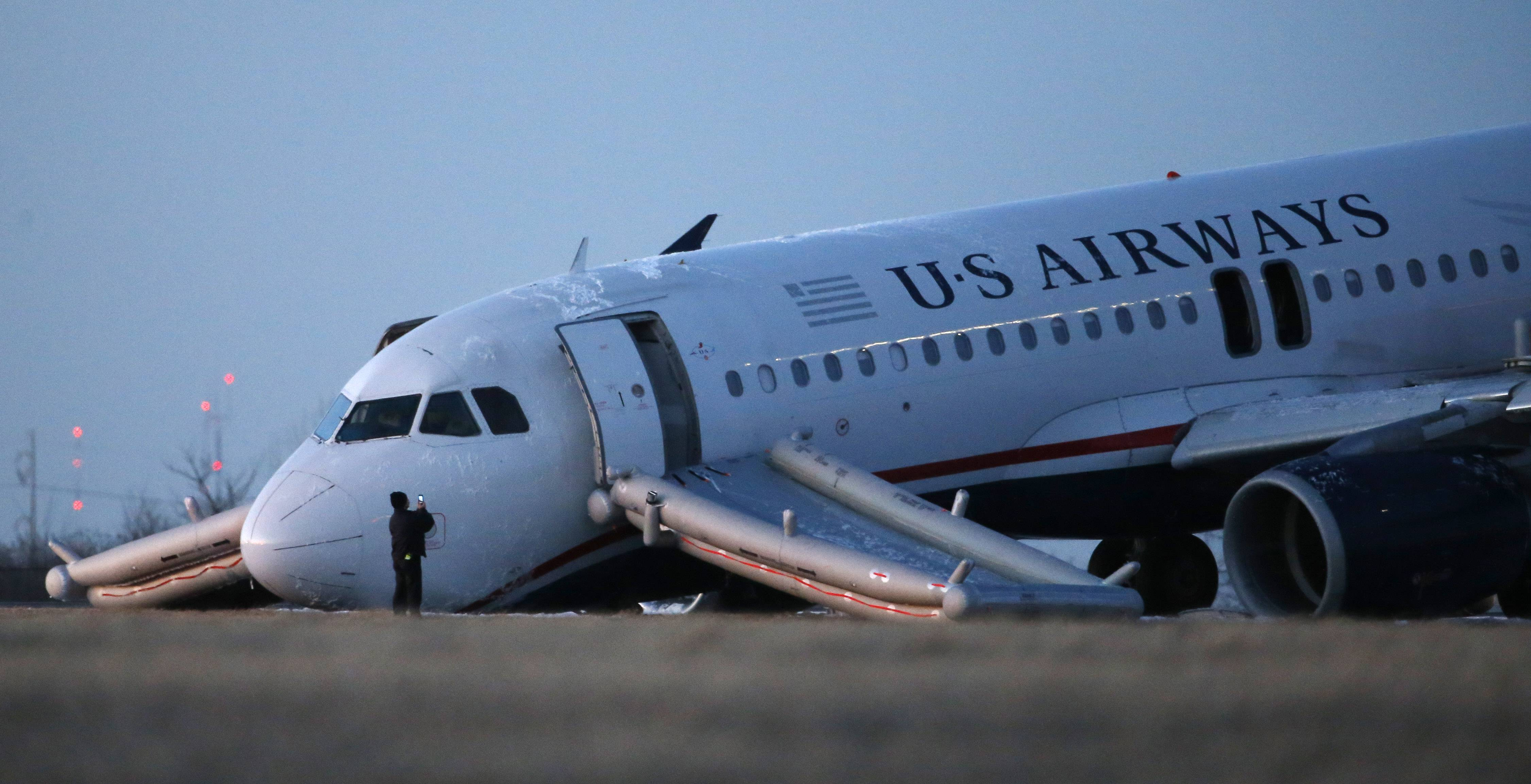 A person takes a photo of a damaged US Airways jet at the end of a runway at the Philadelphia International Airport, Thursday, March 13, 2014, in Philadelphia. Airline officials said the flight was heading to Fort Lauderdale, Fla., when the pilot was forced to abort takeoff around 6:30 p.m., after the front landing gear failed. An airport spokeswoman said no injuries have been reported.
