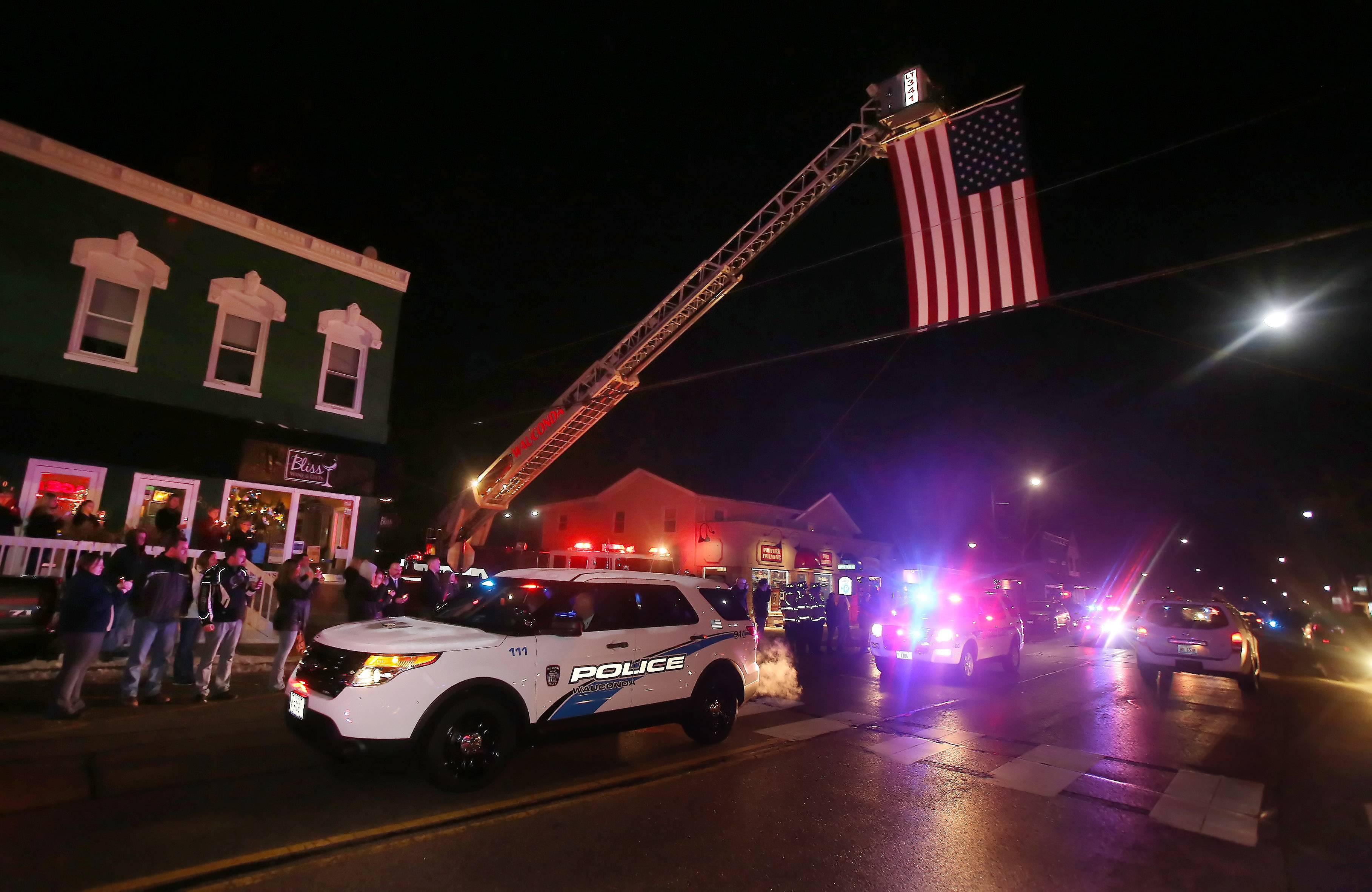 A procession of police and sheriff's cars drive under an American flag displayed by the Wauconda Fire Department as they escort the body of Wauconda police officer Eric Schultz through downtown after a funeral held at the Wauconda High School Thursday night. Schultz died after a lengthy battle with cancer.