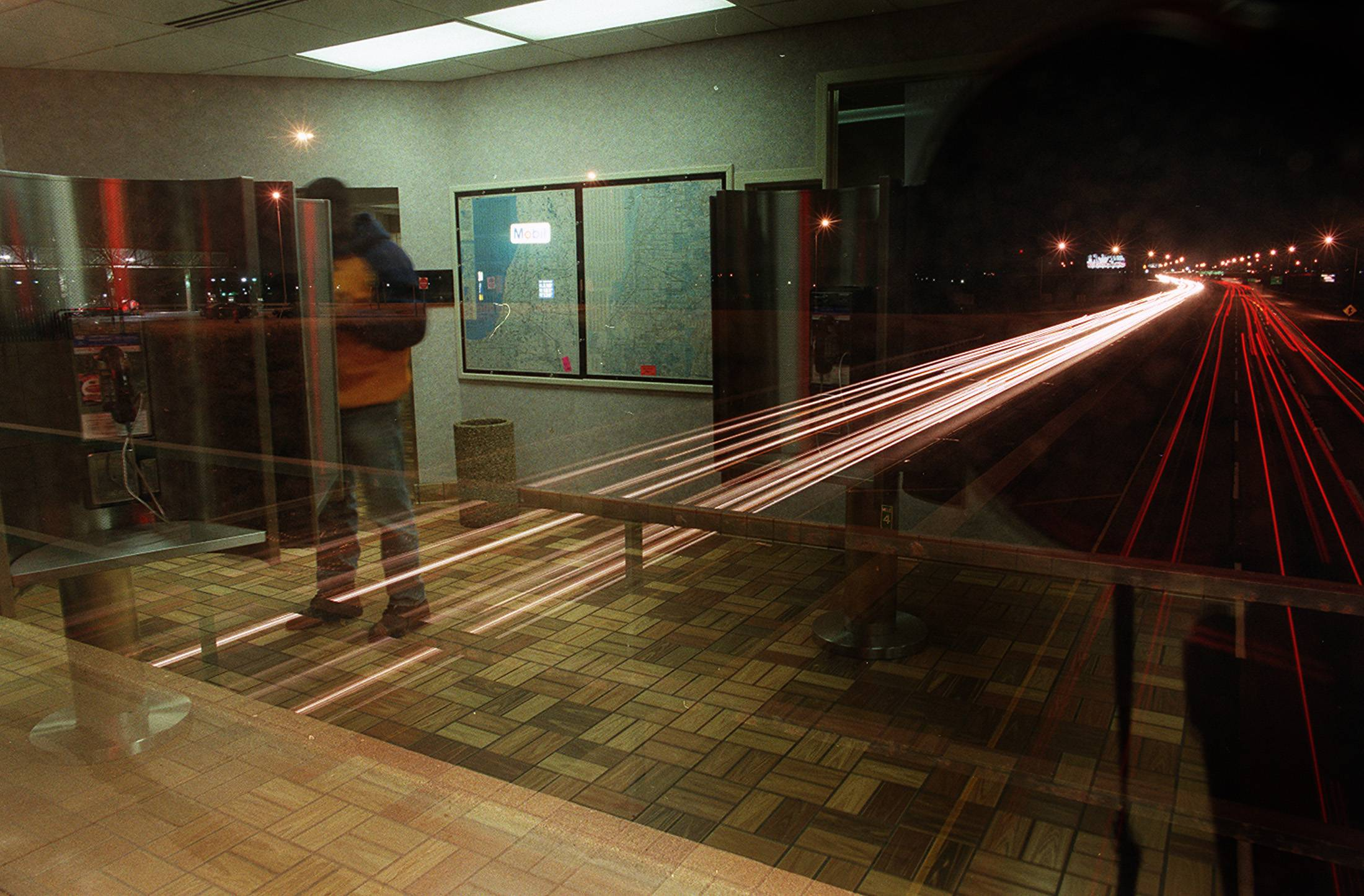 Reflected in glass as traffic passes underneath, a customer uses the phone at the Des Plaines Oasis.