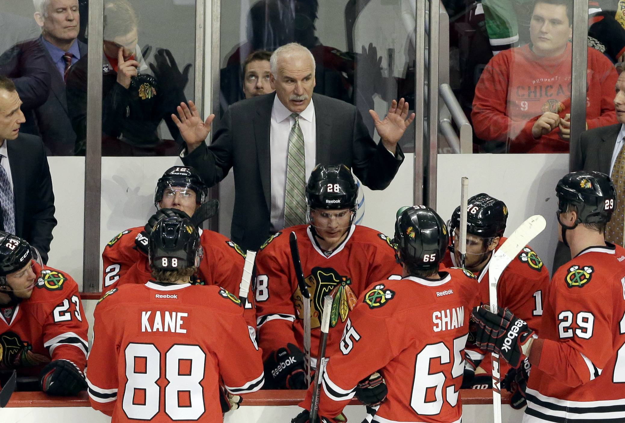 Blackhawks head coach Joel Quenneville, top, talks to his team during the third period of an NHL hockey game against the Nashville Predators in Chicago, Friday, March 14, 2014. The Predators won 3-2.