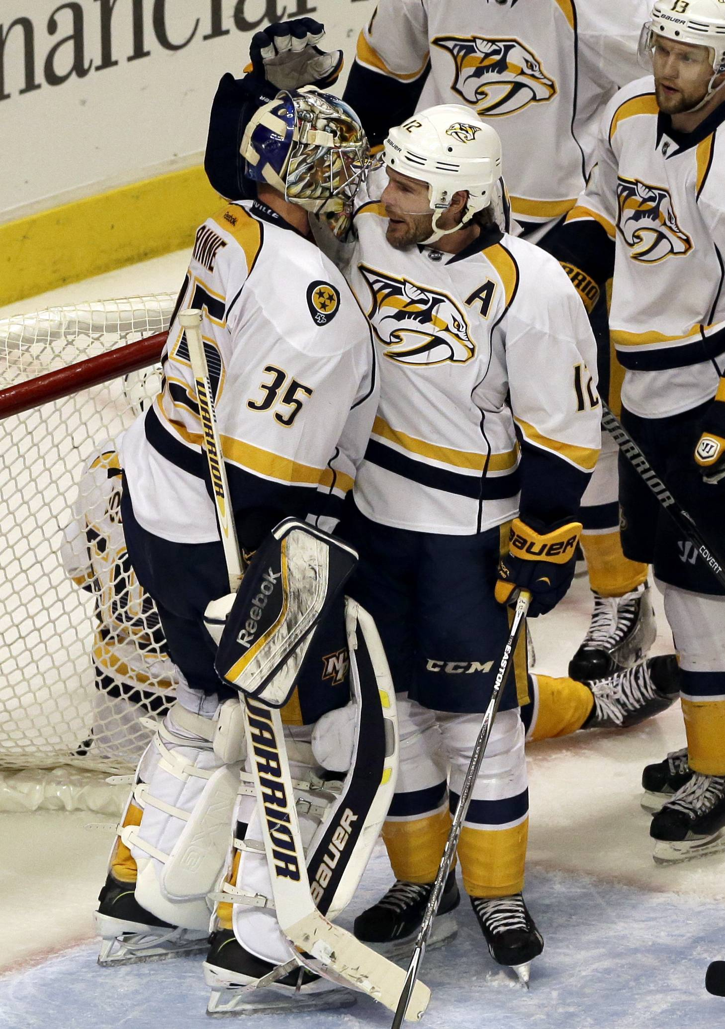 Nashville Predators goalie Pekka Rinne (35) celebrates with Mike Fisher (12) after they defeated the Chicago Blackhawks 3-2 during an NHL hockey game in Chicago, Friday, March 14, 2014.