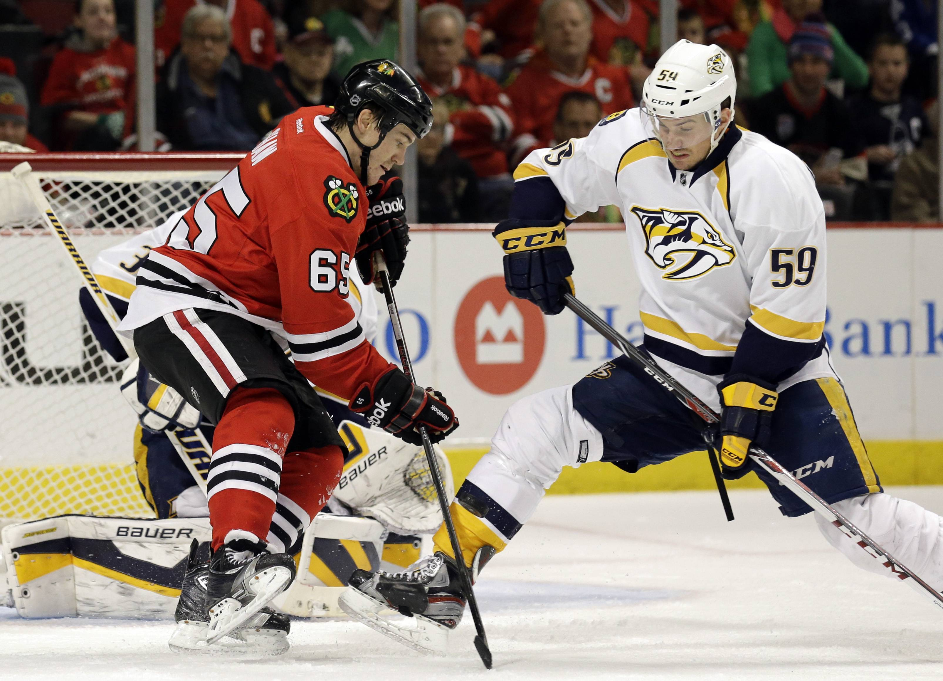 Chicago Blackhawks' Andrew Shaw (65), left, controls the puck against  Nashville Predators' Roman Josi (59) during the second period of an NHL hockey game in Chicago, Friday, March 14, 2014. The Predators won 3-2.