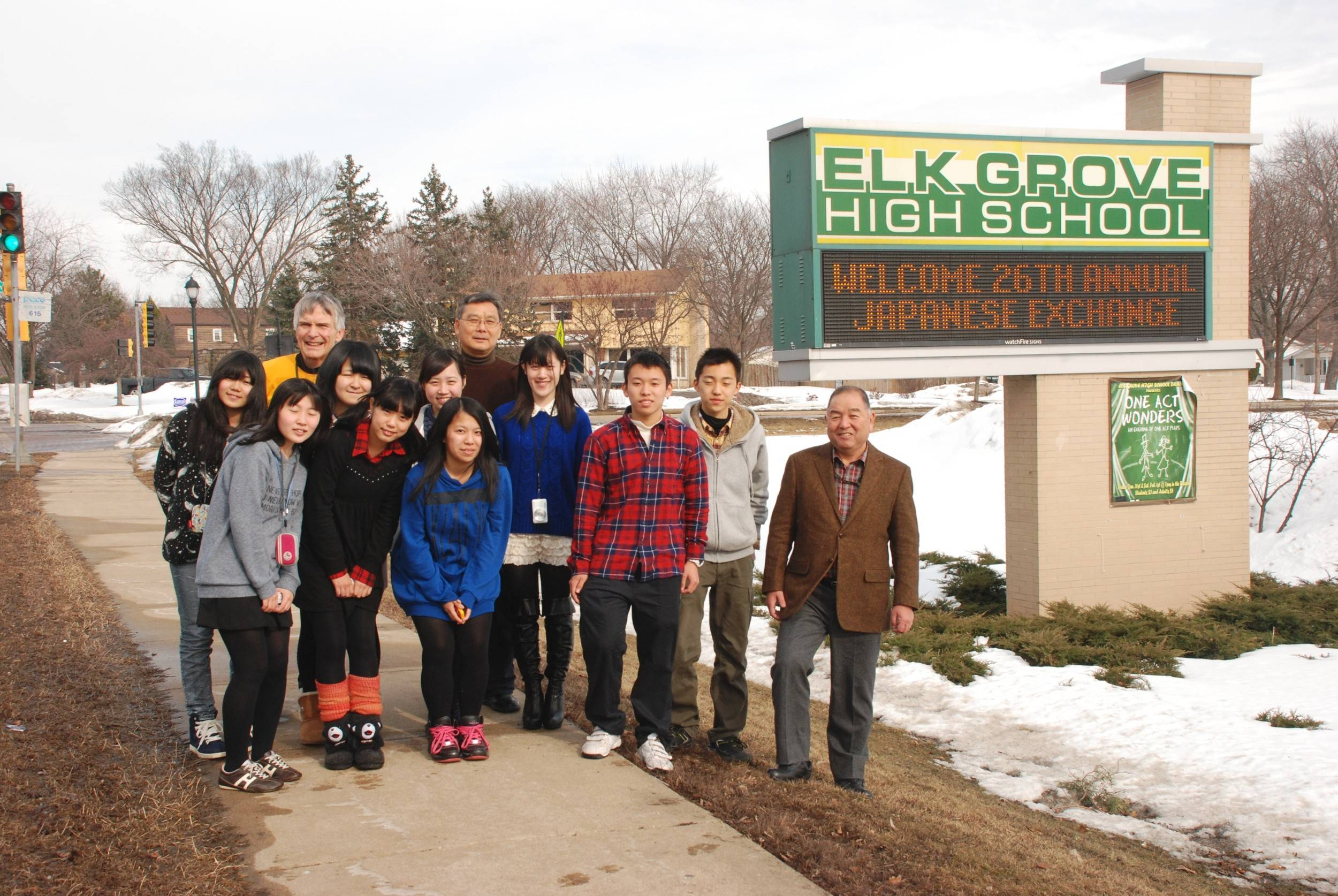 A group of students from Japan visiting Elk Grove High School gather by the school sign with Elk Grove teacher and Japanese program coordinator Cliff Darnall.