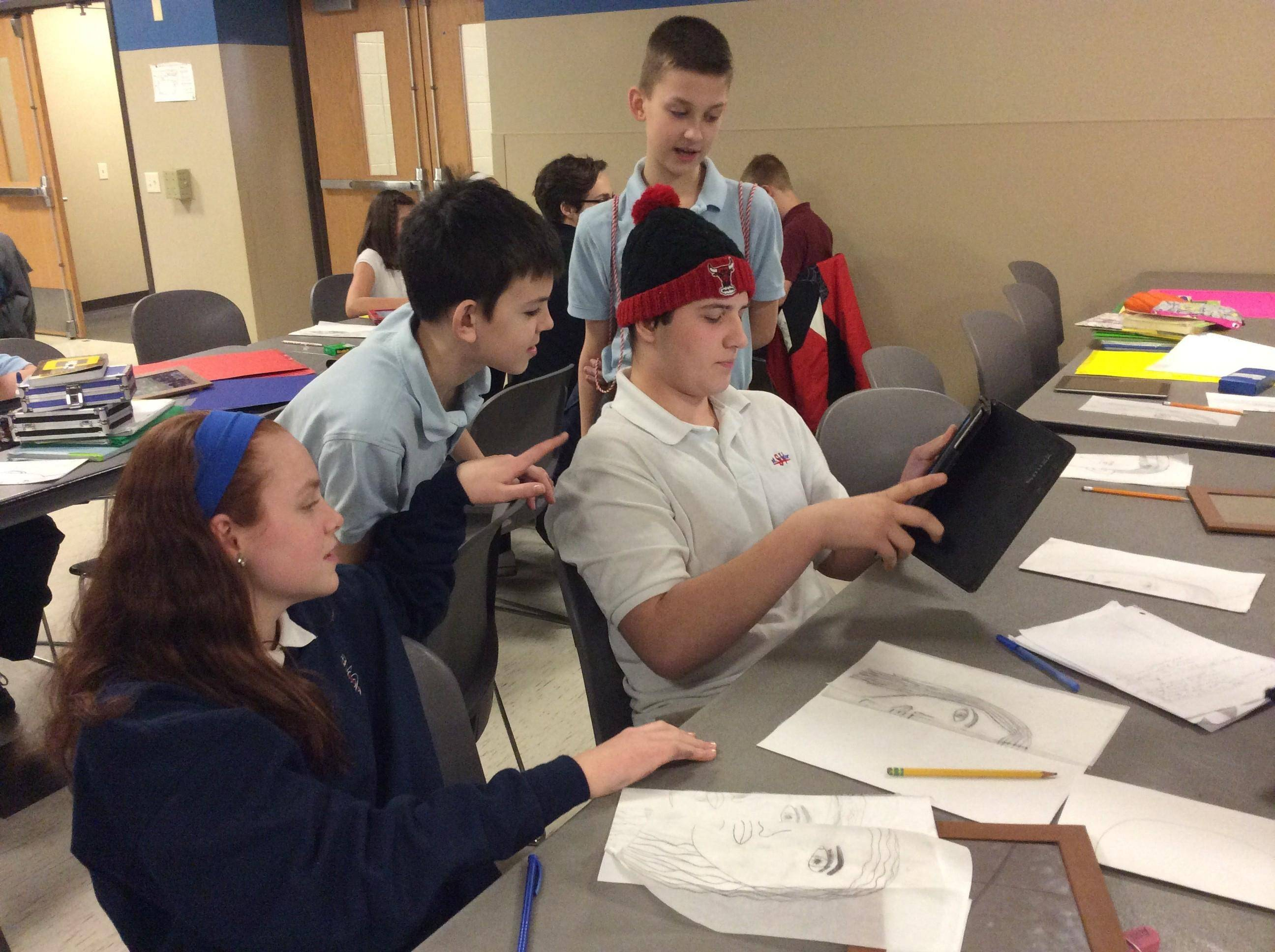 St. James School students look over the shoulder of a Saint Viator High School student as they work on collaborative self-portraits to be featured in The Arts in Concert March 18.