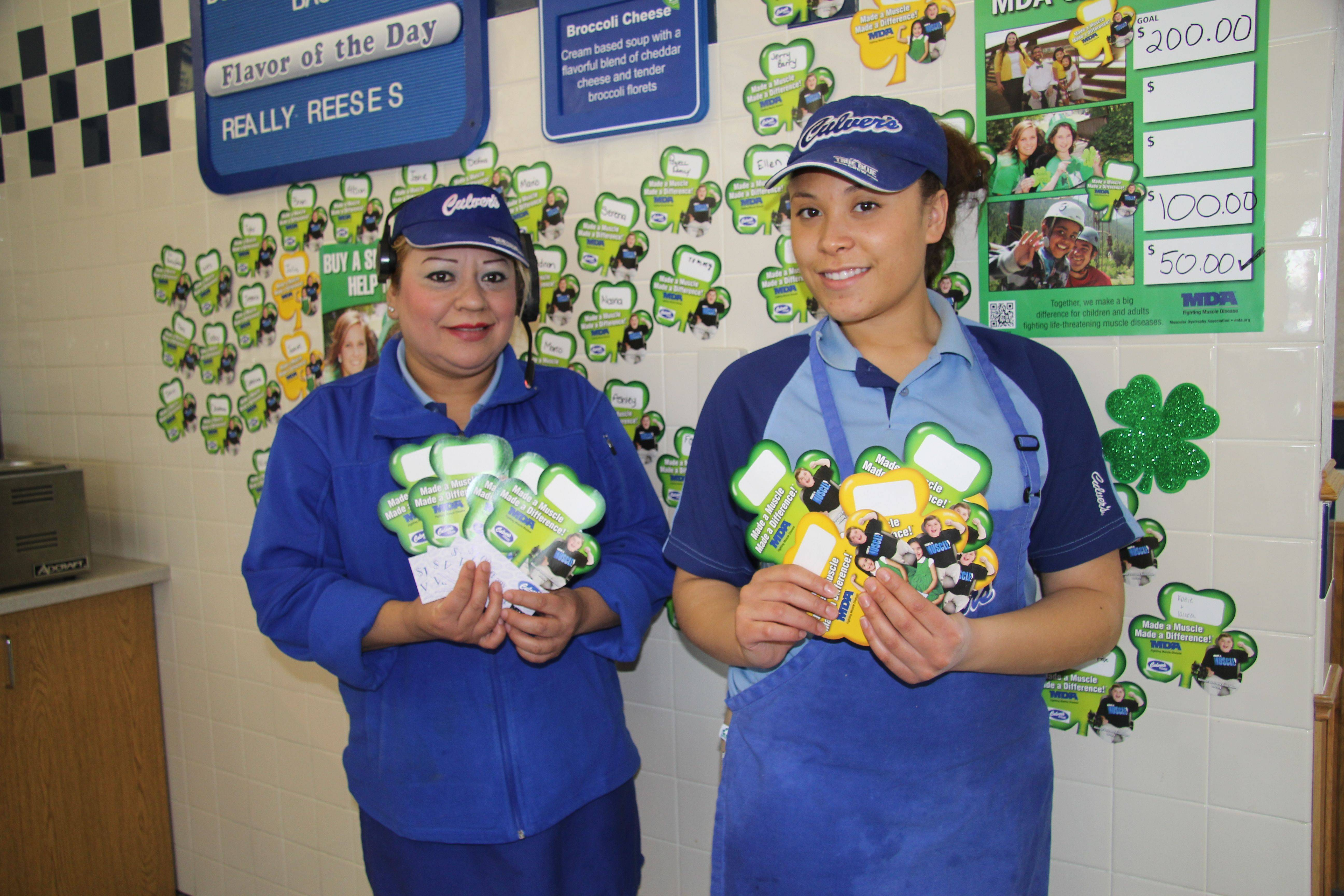 Norma Diaz (L) and Christina Holland (R), Team Members at Culver's of Carpentersville, show off the store's shamrocks supporting Muscular Dystrophy Association.