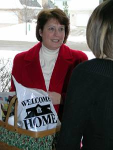 Jennifer Zack, president of Welcome Home Batavia and North Aurora, presents welcome packets to newcomers. The firm celebrates 15 years in business in March.