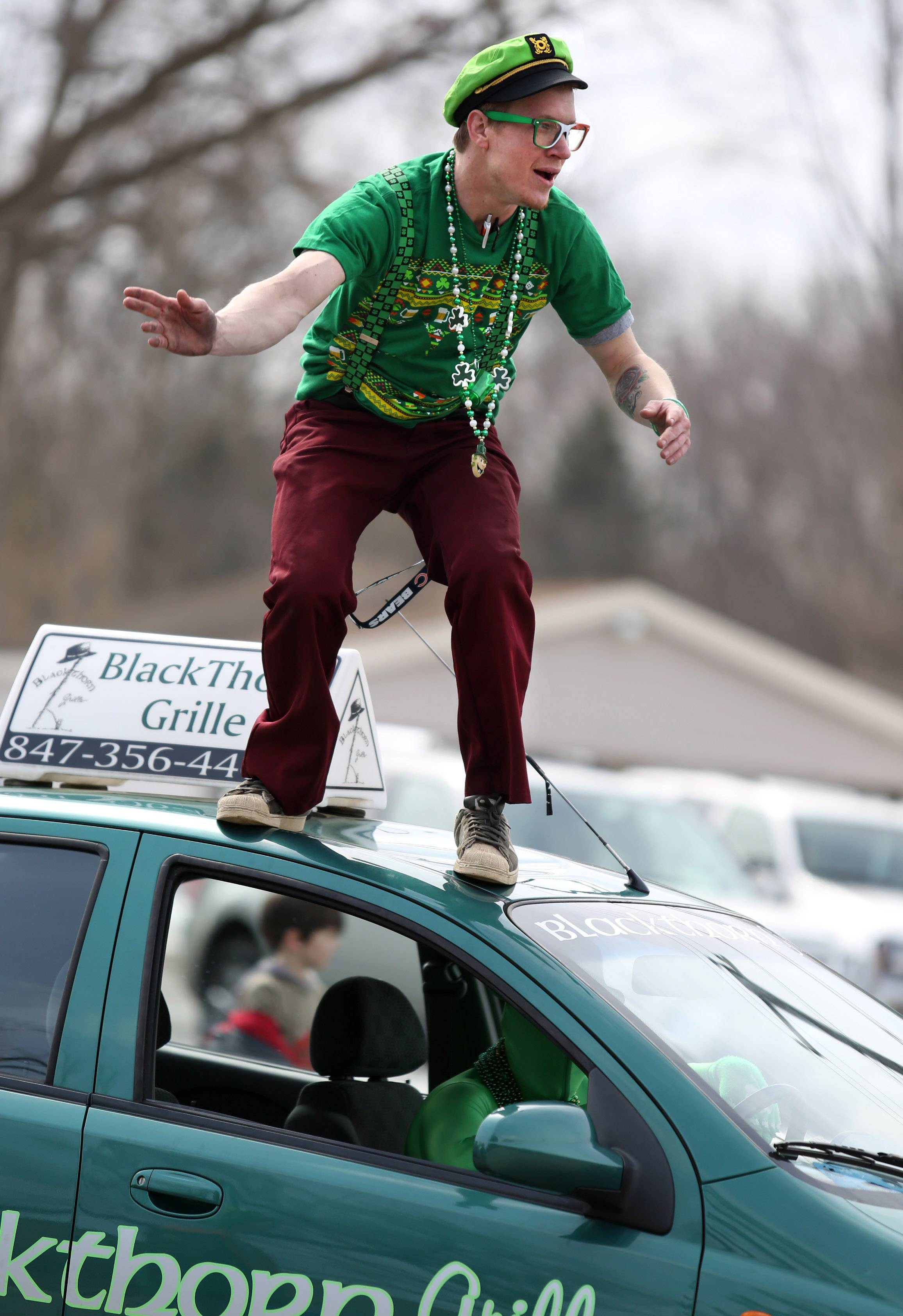 Patrick McLaughlin car surfs on Blackthorn Grille's car with Ryan Coy driving in the Village of Lake Villa's St. Patrick's Day Parade on Saturday.