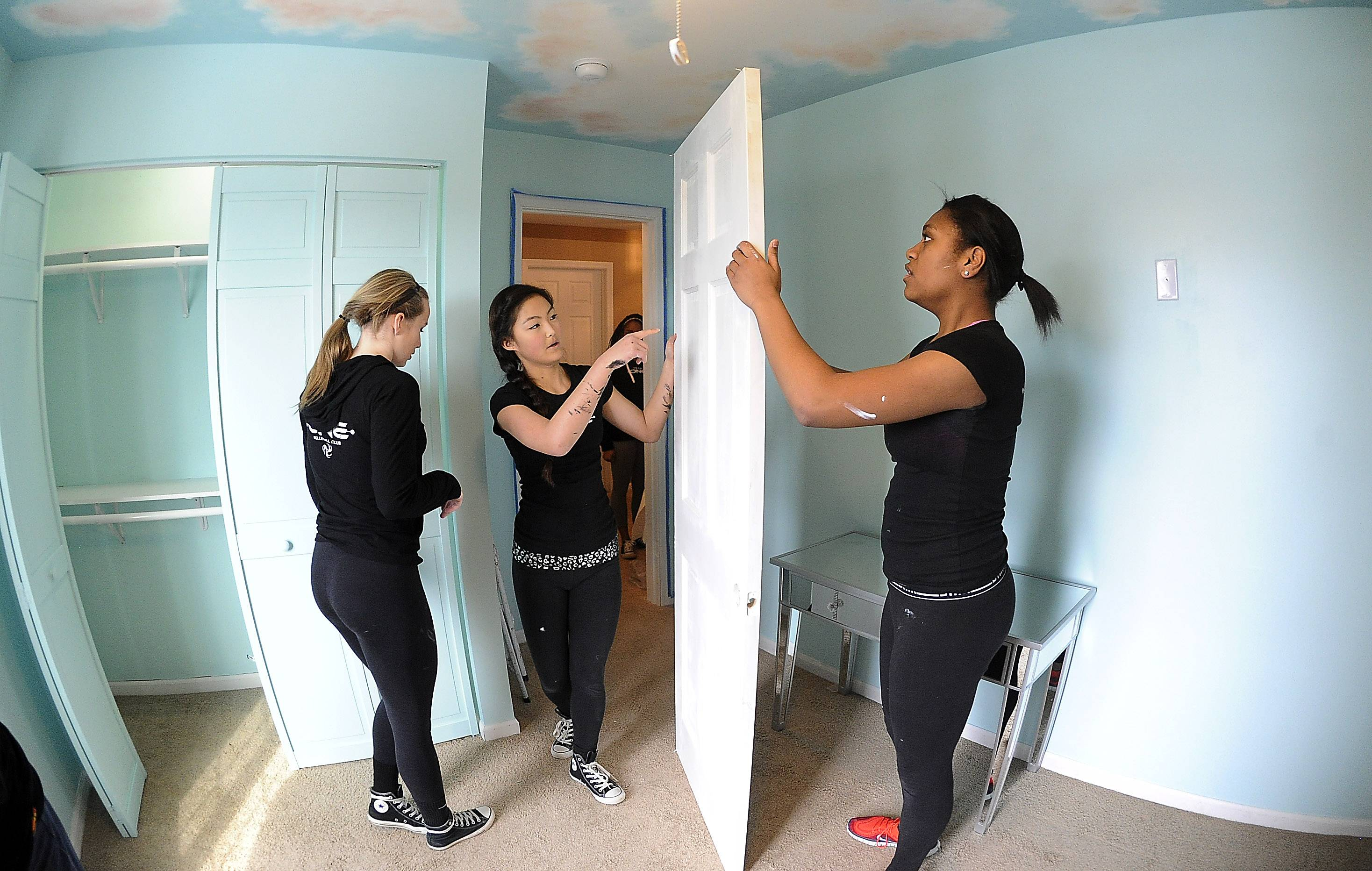 Asia Green, right, from Plainfield and her fellow teammates of Team One Volleyball Club in Aurora, Cerina Myong of Naperville, middle, and Sarah Pliml of Naperville work on the freshly painted door Saturday that is part of the makeover for a Bartlett girl with a life-threating medical condition.