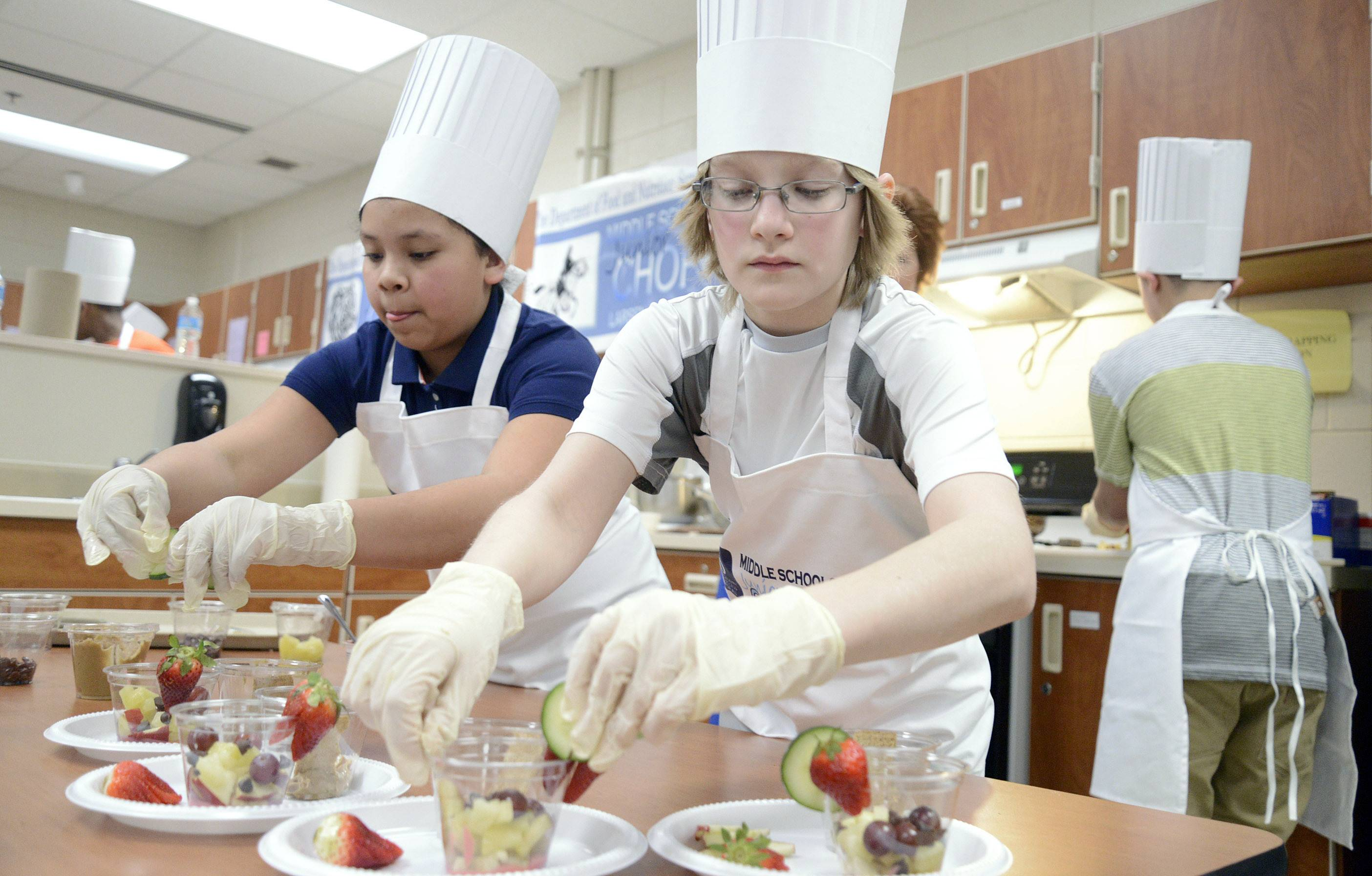 "Reyna Soto, 12, left, and Alex Wirsing, 13, decorate snack cups while teammate Alex Kunicki, 13, chops more fruit for the Larsen Middle School team at the ""Junior Chopped: A Middle School Cooking Competition"" Saturday at South Elgin High School. All three are from Elgin."