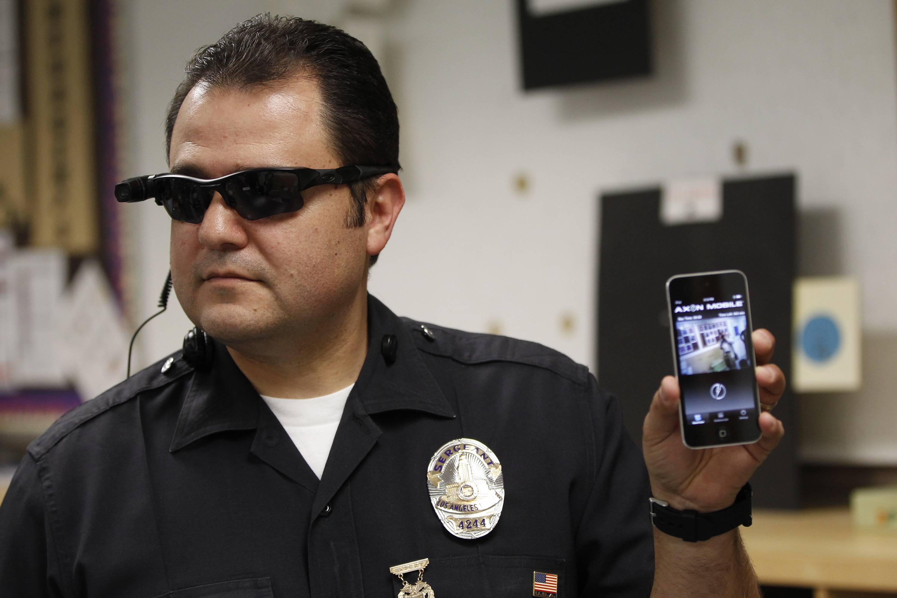 ADVANCE FOR MOVEMENT SATURDAY MARCH 15 - This Jan. 15, 2014 file photo shows Los Angeles Police Sgt. Daniel Gomez demonstrating a video feed from his camera into his cellphone as on-body cameras are demonstrated for the media in Los Angeles. Thousands of police agencies have equipped officers with cameras to wear with their uniforms, but they've frequently lagged in setting policies on how they're used, potentially putting privacy at risk and increasing their liability. As officers in one of every six departments across the nation now patrols with tiny lenses on their chests, lapels or sunglasses, administrators and civil liberties experts are trying to envision and address troublesome scenarios that could unfold in front of a live camera. (AP Photo/Damian Dovarganes)