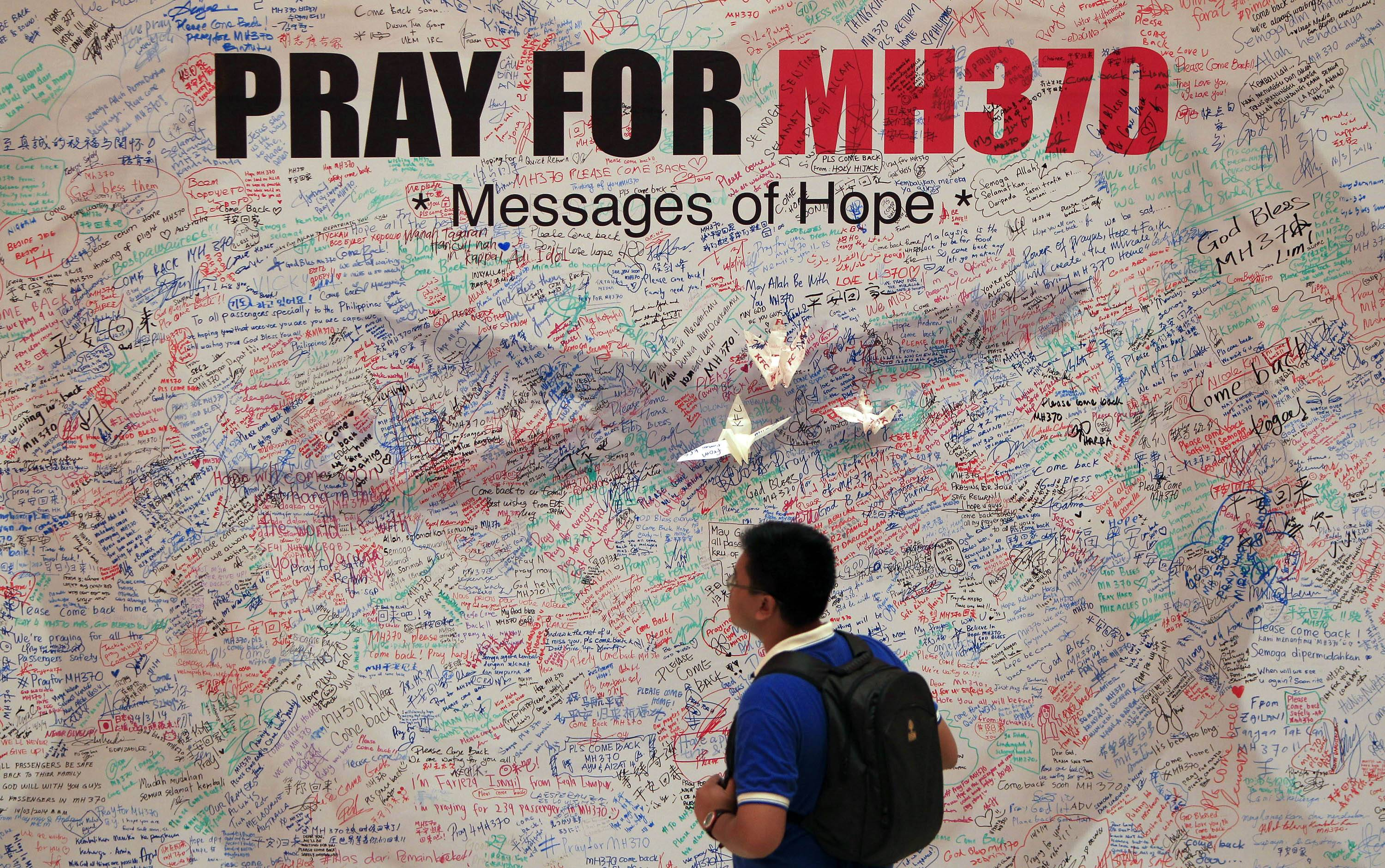 A man reads messages for passengers aboard a missing Malaysia Airlines plane at a shopping mall in Kuala Lumpur, Malaysia, Saturday.