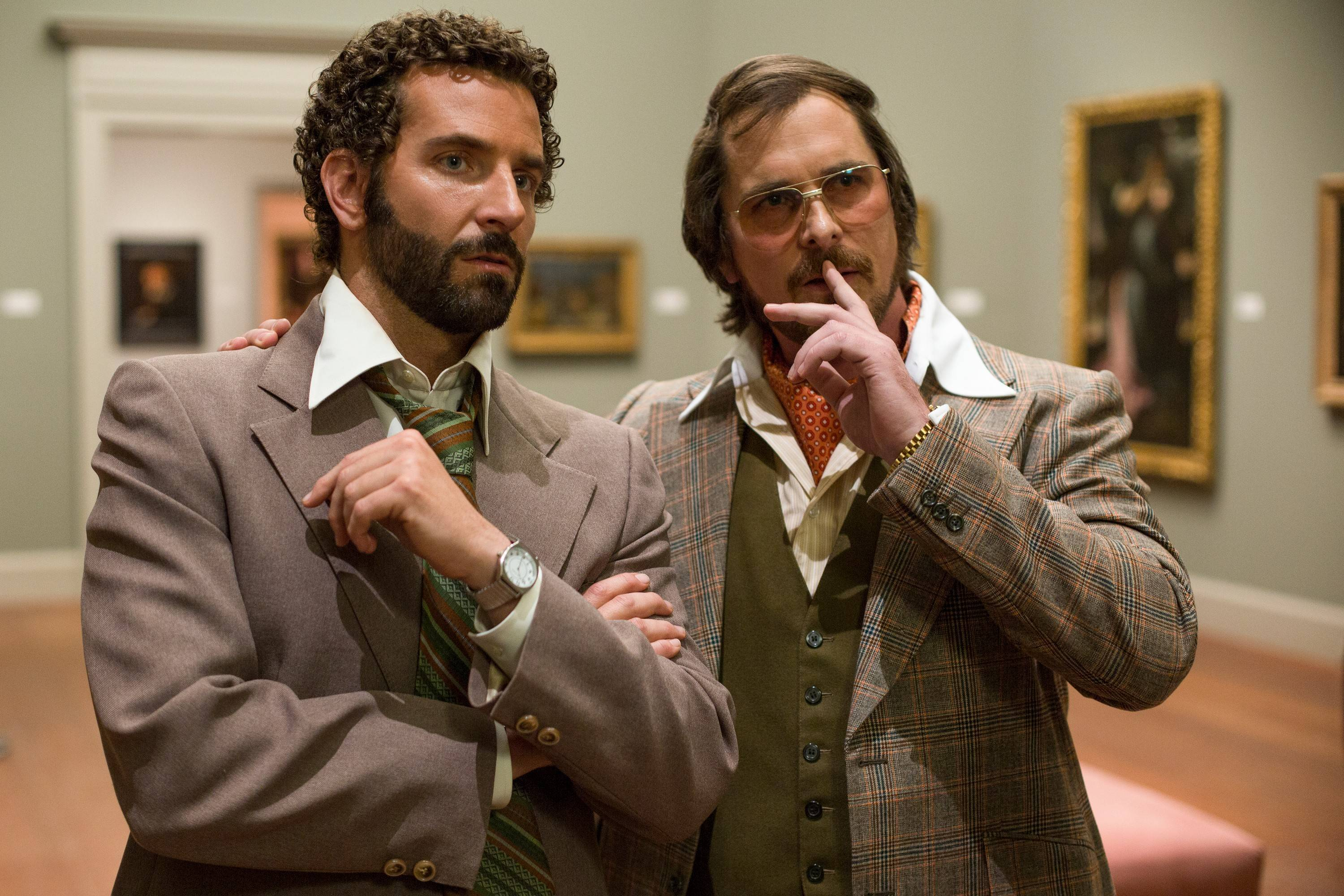 "An agent (Bradley Cooper), left, recruits a con man (Christian Bale) for a sting operation in ""American Hustle."""