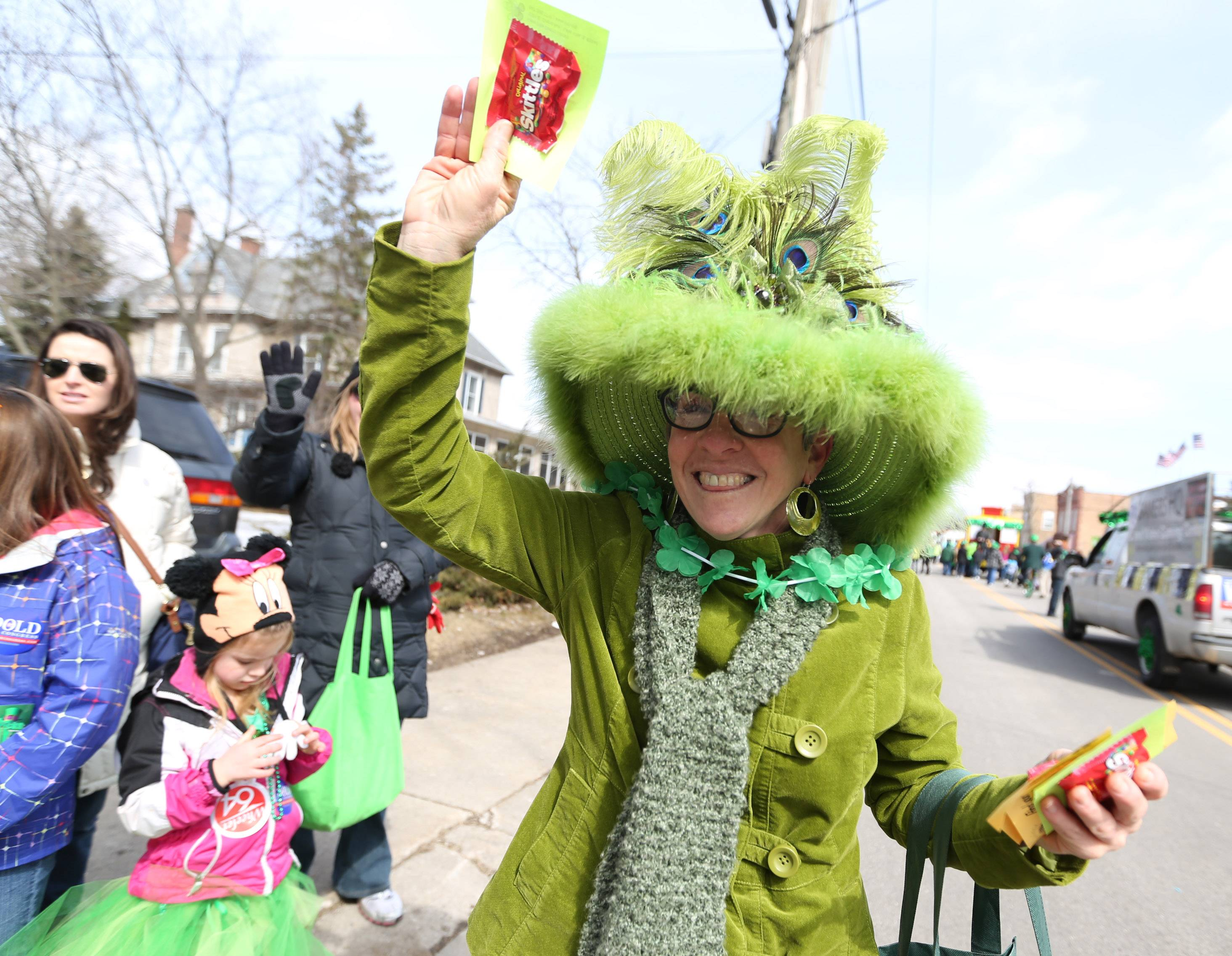 Sheri Conner throws candy while marching with the Lake Villa District Library in the Village of Lake Villa's St. Patrick's Day Parade on Saturday.