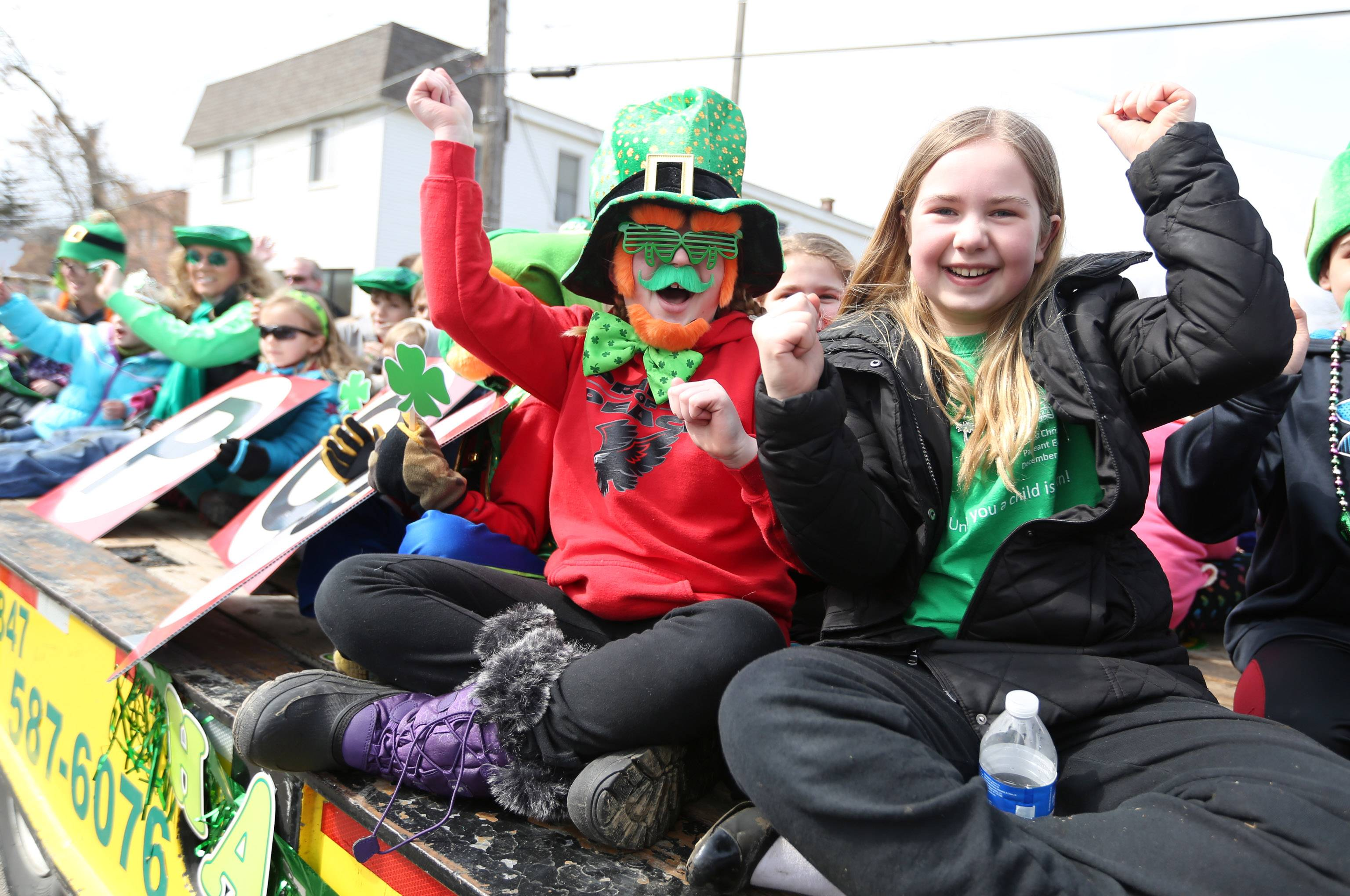 Taylor Graf and Jane Makela, both 11 and of Lake Villa, wave to parade goers while riding on Fox Recovery and Towing's flatbed truck in the Village of Lake Villa's St. Patrick's Day Parade on Saturday.