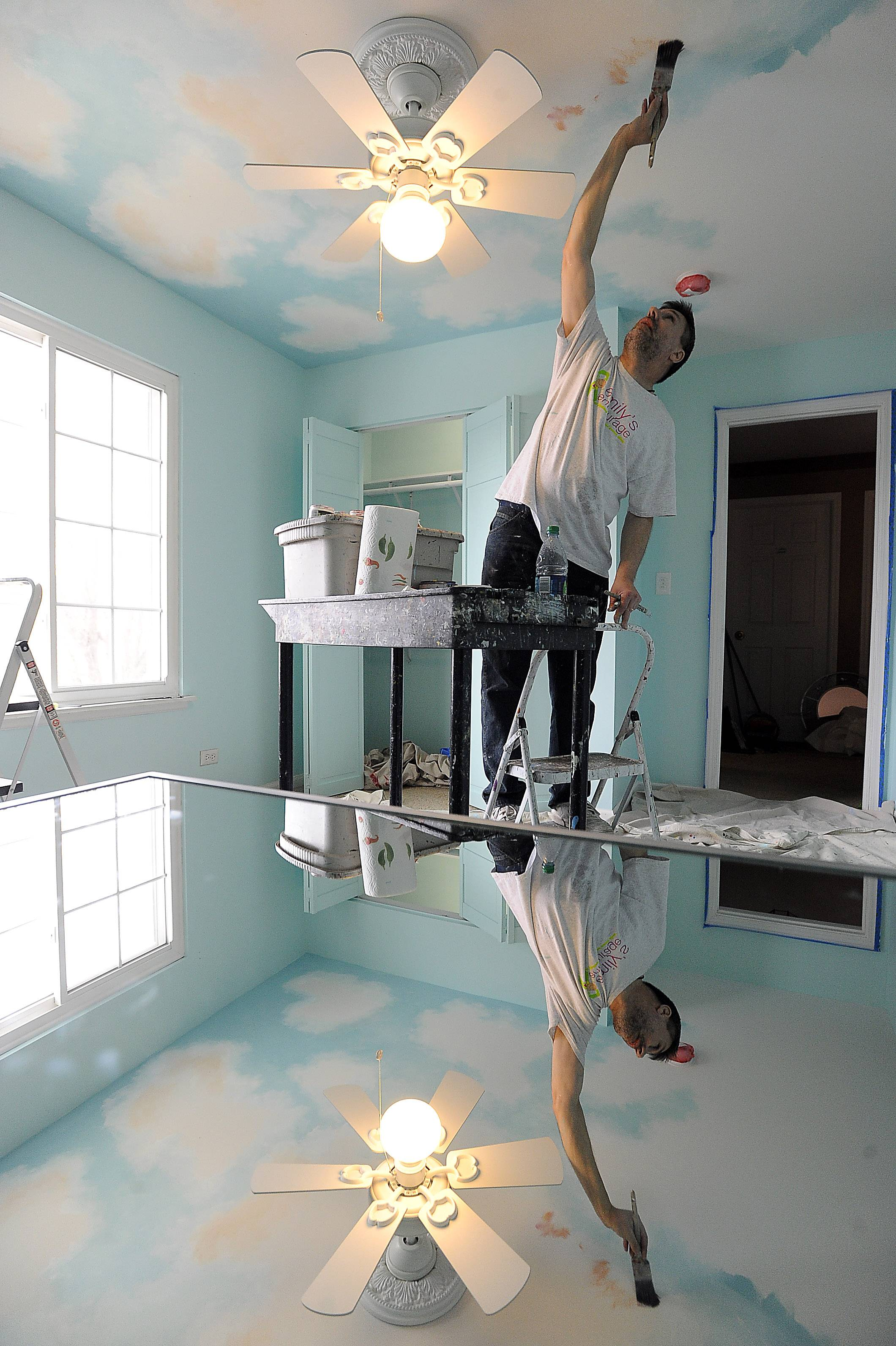 Ken Markiewicz of Naperville works on his ceiling mural masterpiece Saturday that is part of the makeover for a Bartlett girl with a life-threating medical condition.