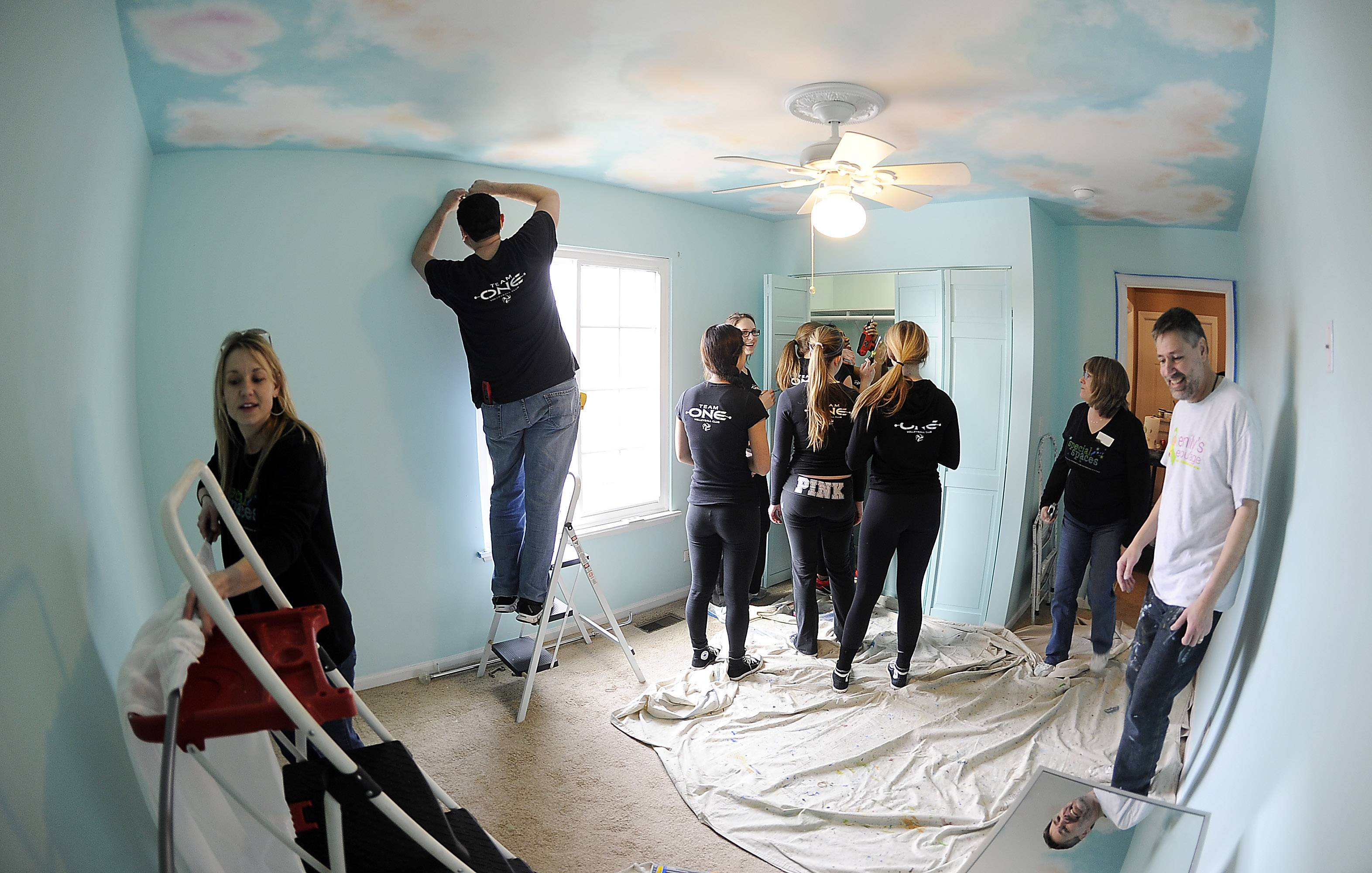 Members of Team One Volleyball club and other personnel work at a fever pitch level trying to get a bedroom makeover done Saturday for a Bartlett girl with a life-threating medical condition.