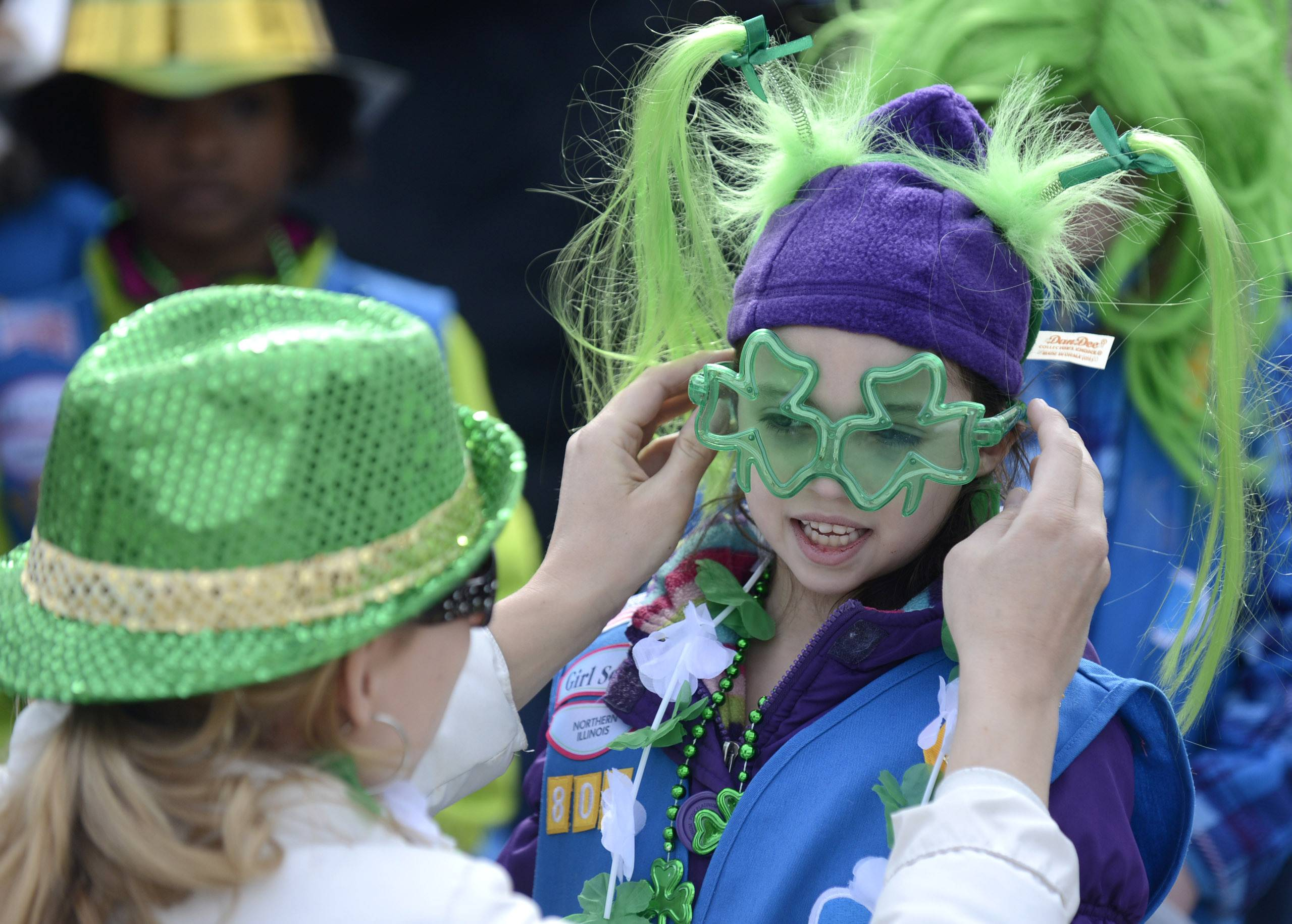 Bianca Santucci, 6, of St. Charles, has her shamrock sunglasses adjusted by her mother, Dawn, while they wait to walk with Girl Scout Troop 830 in the St. Patrick's Day parade in St. Charles on Saturday.