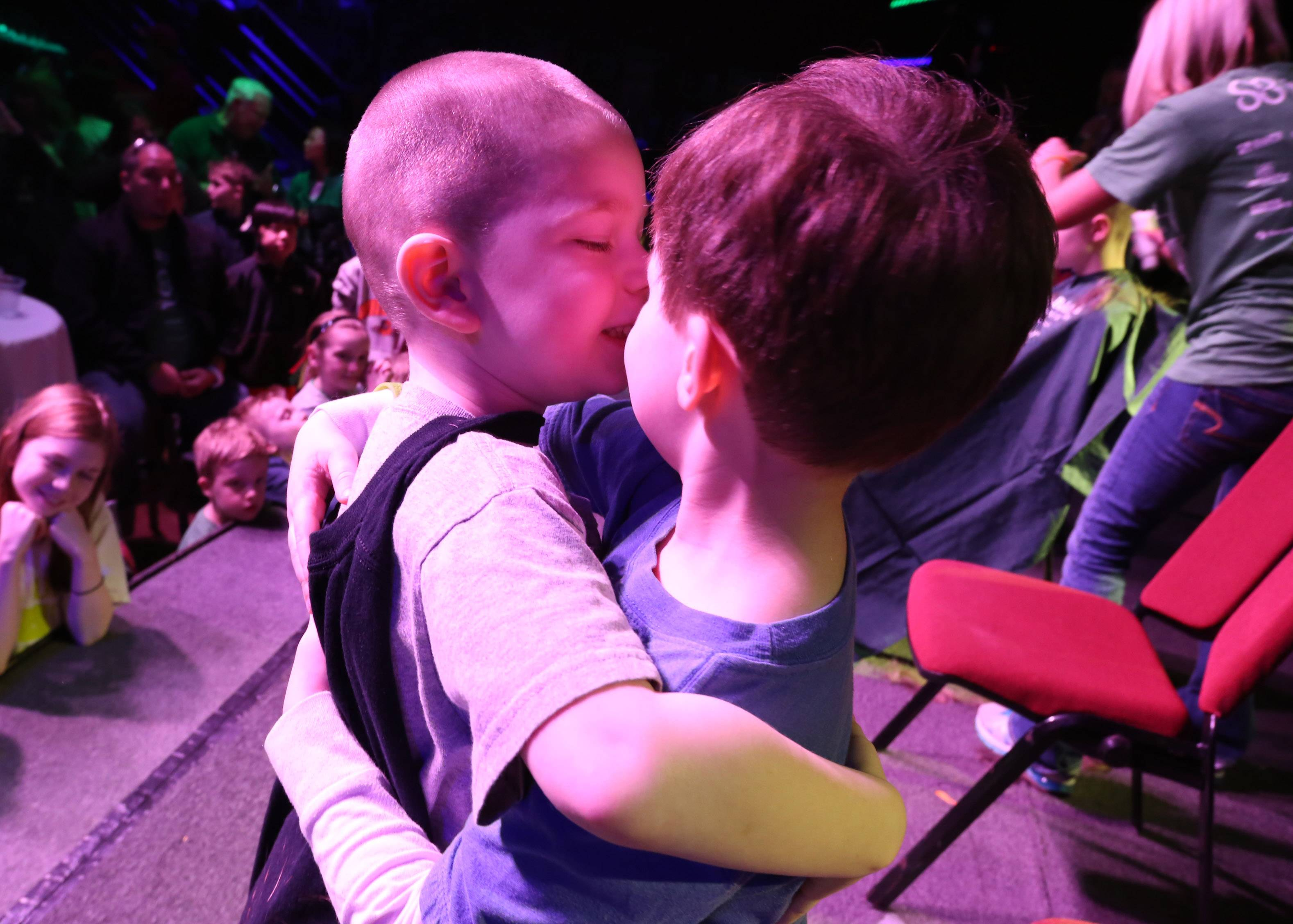 Six-year-old Connor Johnson, a 2001 cancer survivor of Libertyville, right, gets a hug from friend Luke Steres, 4, of Gurnee, after Connor shaved Luke's head during a St. Baldrick's Foundation event at Austin's Saloon and Eatery on Saturday in Libertyville.