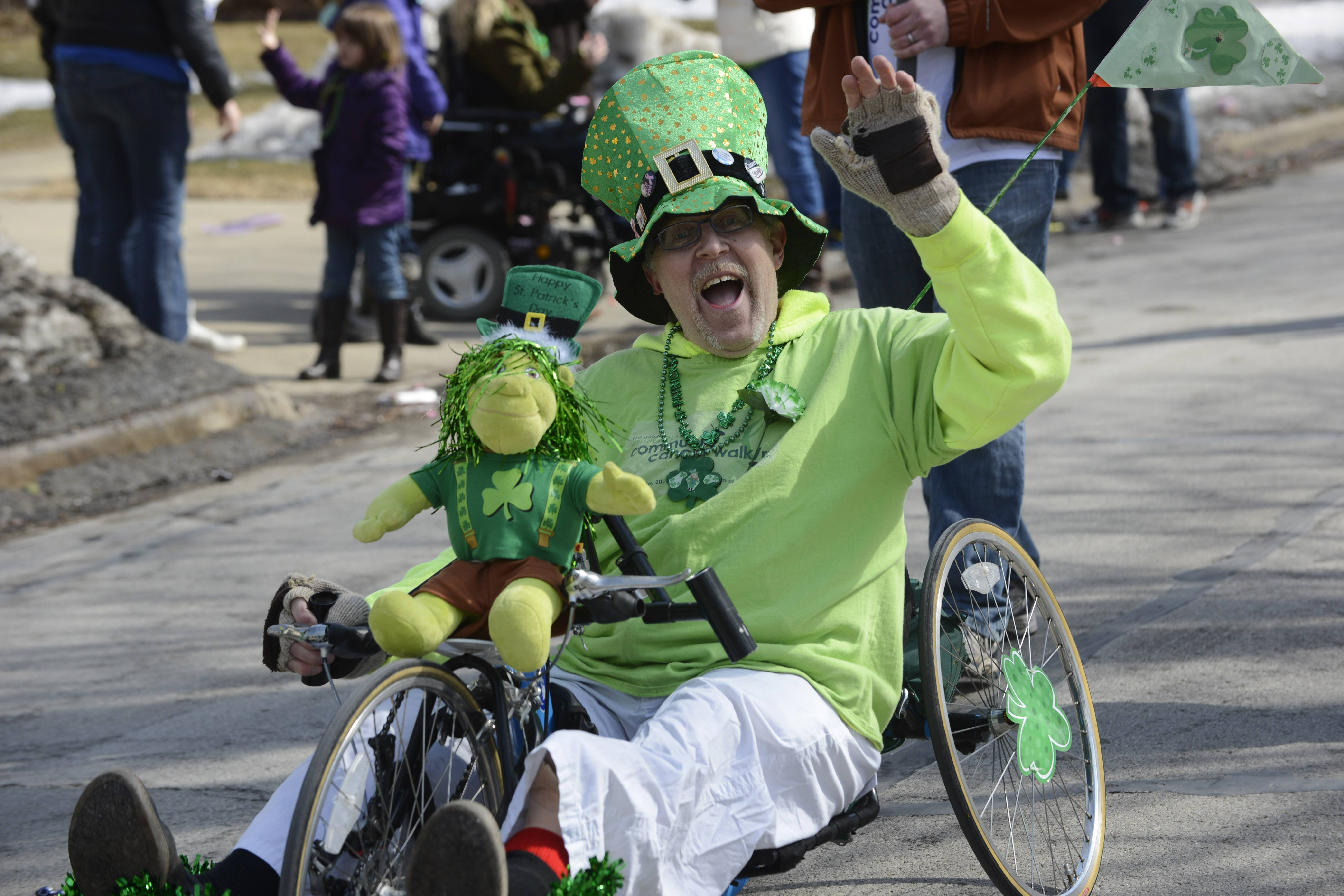 Thomas Hoff, a volunteer with the Wellness Place, waves to onlookers along Wood Street as he rides a handcycle during the Palatine St. Patrick's Day Parade Saturday.