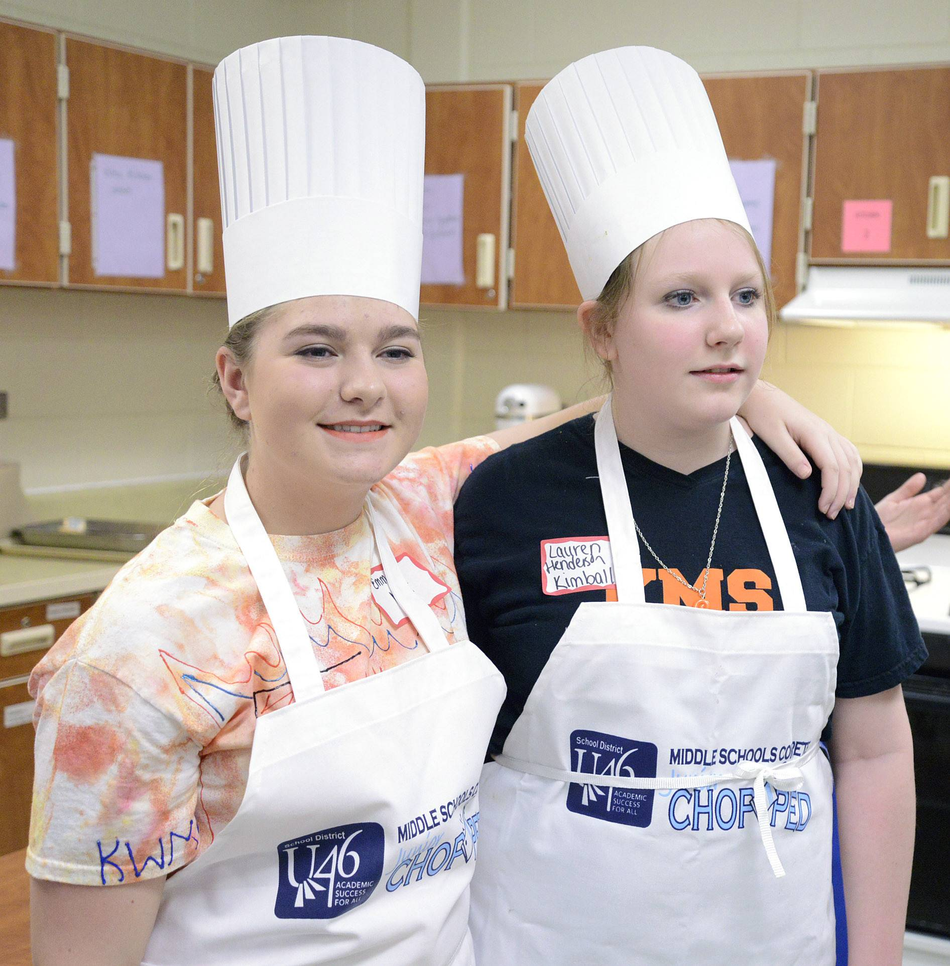 "Emma Miller, 13, of team ""Fire and Ice"" from Kenyon Woods Middle School, left, puts her arm around friend and fellow competitor Lauren Henderson, 14, of ""Team Royals"" from Kimball Middle School, as they await judges' reactions to the food at the ""Junior Chopped: A Middle School Cooking Competition"" Saturday. Both are from Elgin."