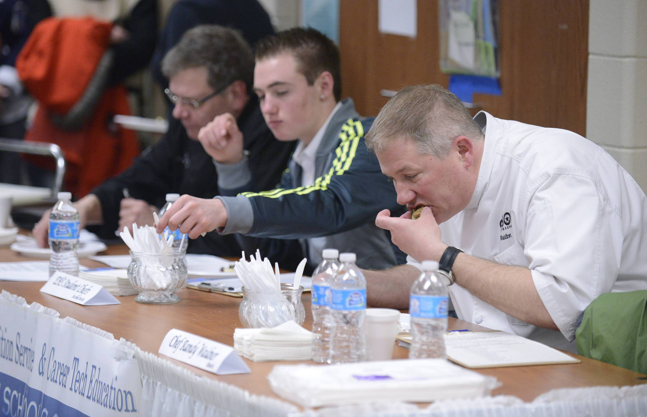 "Gibson's Chef Randy Waidner, far right, and fellow judges sample food at the Elgin Area School District U-46 ""Junior Chopped: A Middle School Cooking Competition"" Saturday at South Elgin High School. Other judges were Chef Bob Janz of Michael's and Associates, left, and Elgin High School freshman Travis Paquin, 16."