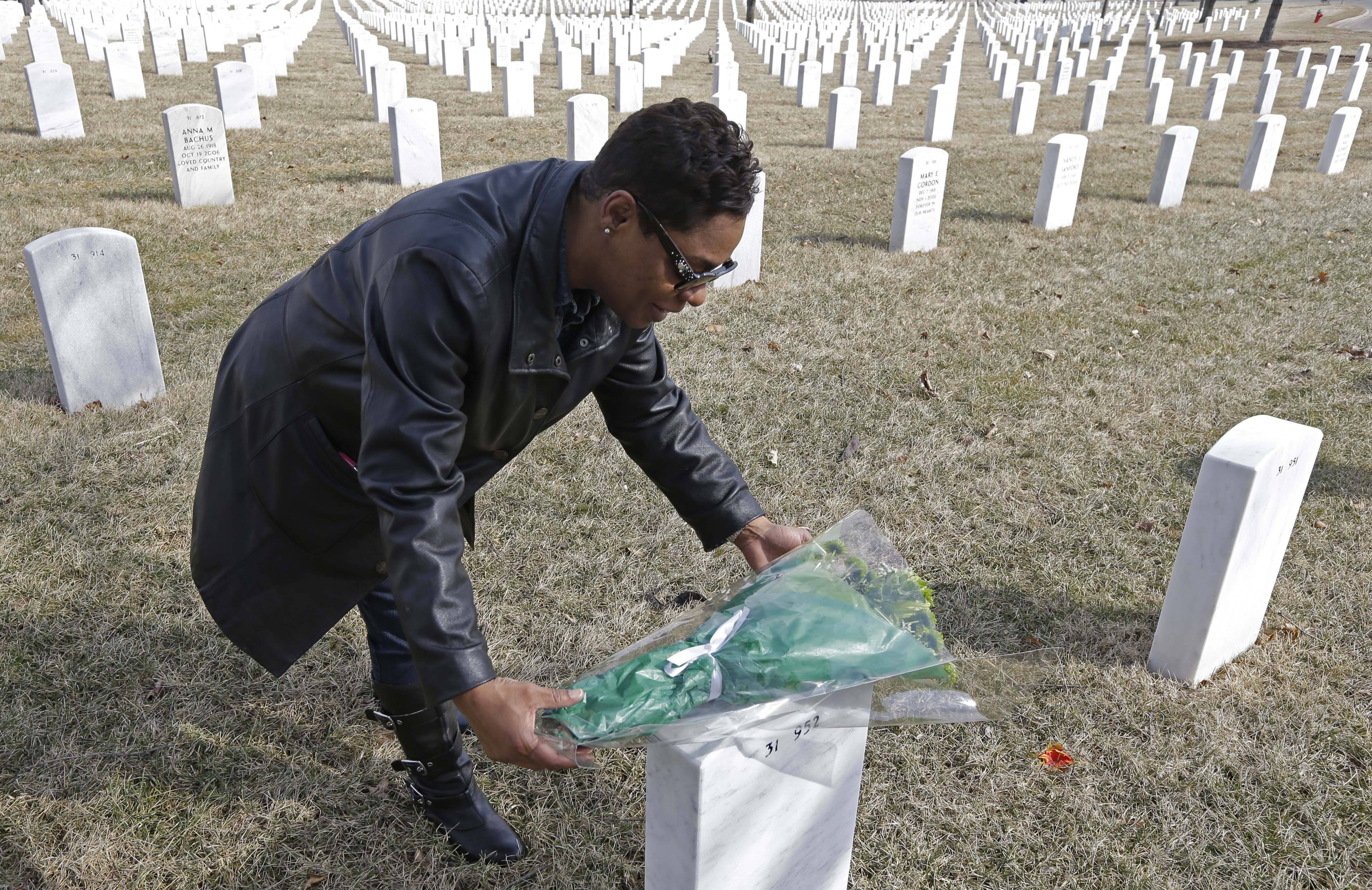 Dellaina Grundy places flowers on her father's headstone, Army veteran Leroy Metcalfe, last Saturday at the Dayton National Cemetery in Dayton, Ohio. Grundy isn't sure whether any or all of the cremated remains buried in the grave are his and knows that mystery will never be solved.