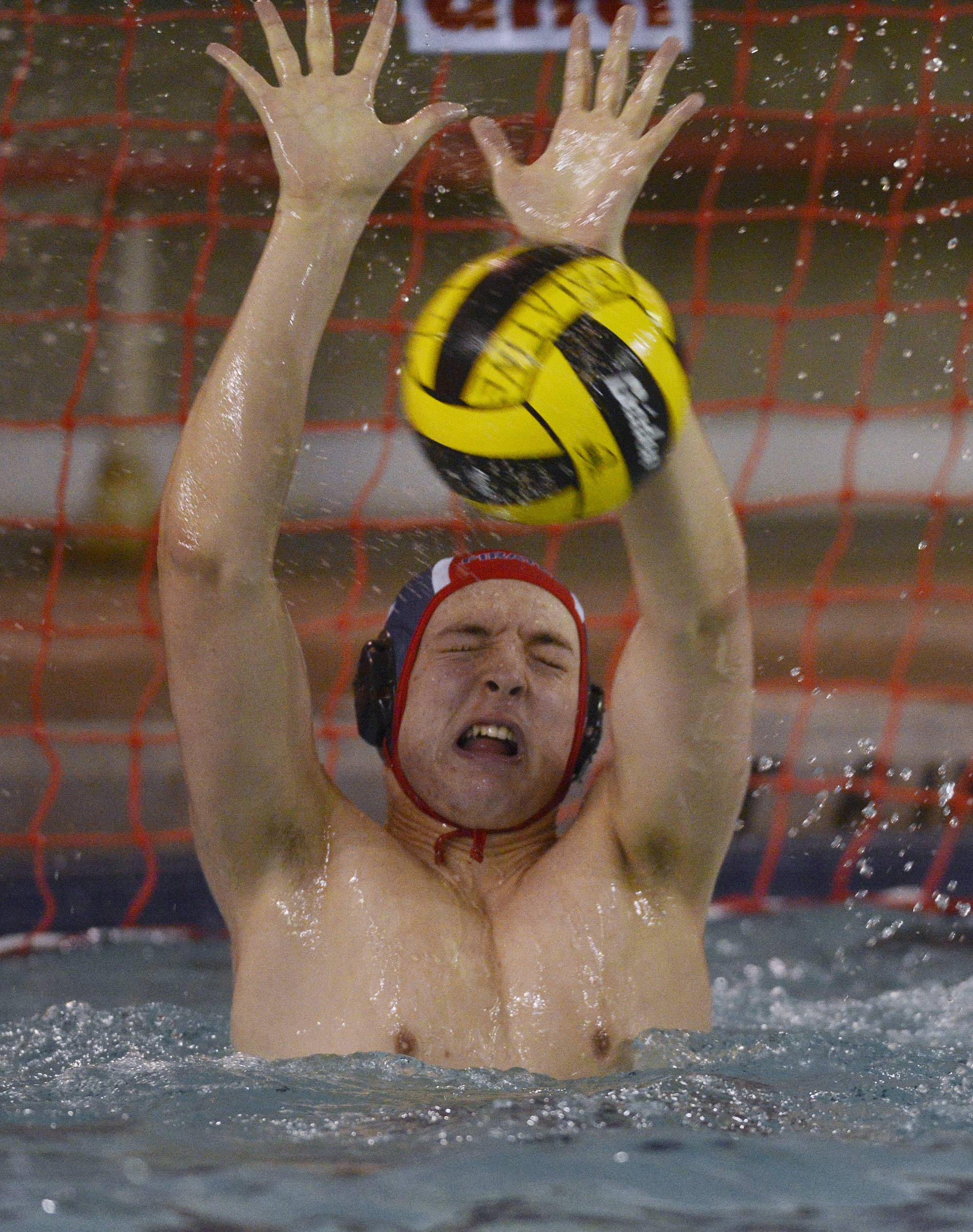 Palatine goalie Colin White makes a save on a shot by McHenry during Saturday's water polo tournament at Palatine.