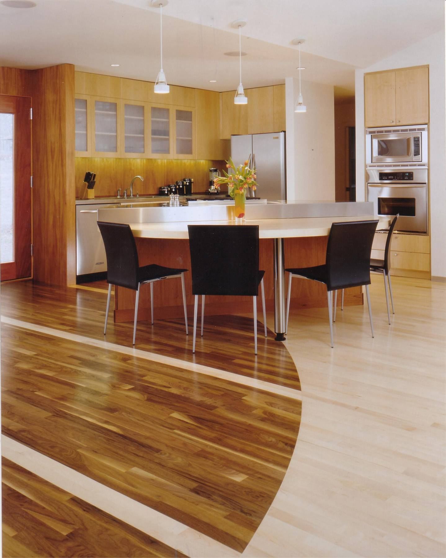 Bleached maple and walnut flooring have been installed in a graceful shape that helps to define two spaces in an open floor plan.