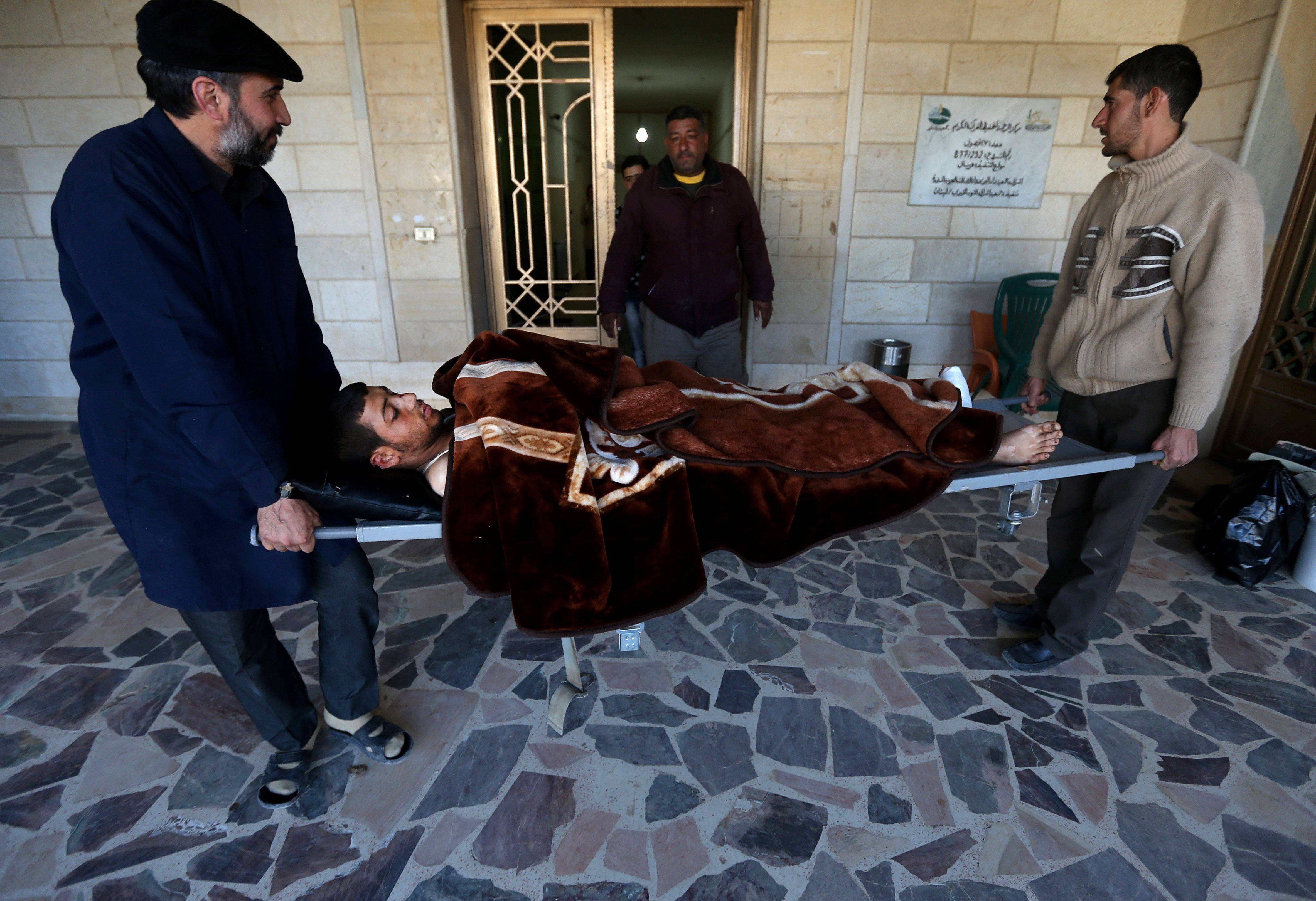 A Lebanese nurse, left, and Syrian man, right, carry Adul-Karim, 18, a Syrian rebel who was injured during a battle against the Syrian government forces and Hezbollah fighters in Rima village near Yabroud ON March 5. Syria said its military seized a key town that served as a rebel supply hub on the Lebanese border on Sunday after a months-long army offensive.